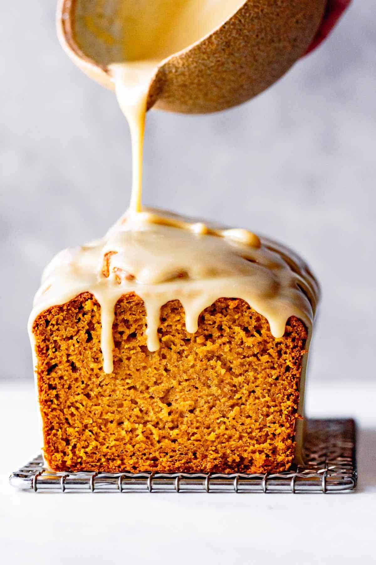 Pouring maple syrup icing on gluten-free dairy-free pumpkin bread