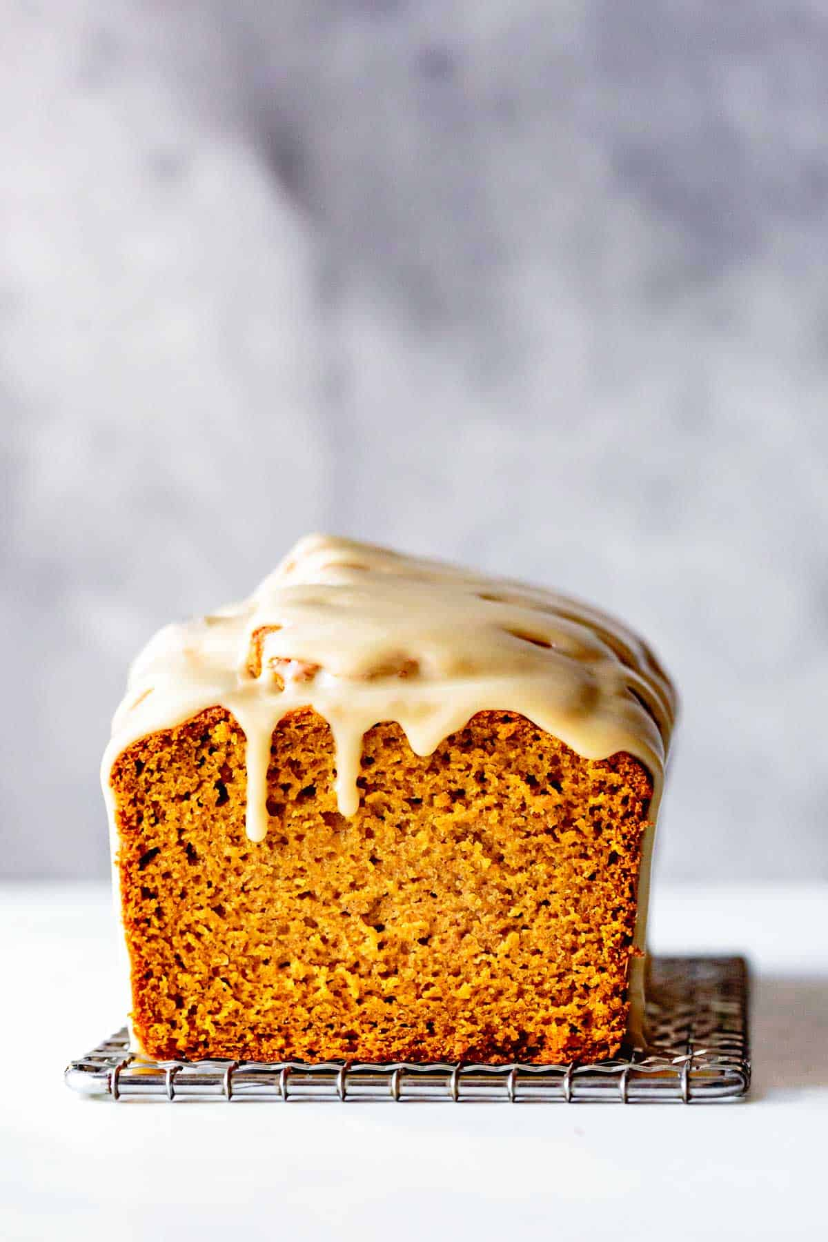 My best gluten free pumpkin bread recipe topped with drippy maple glaze