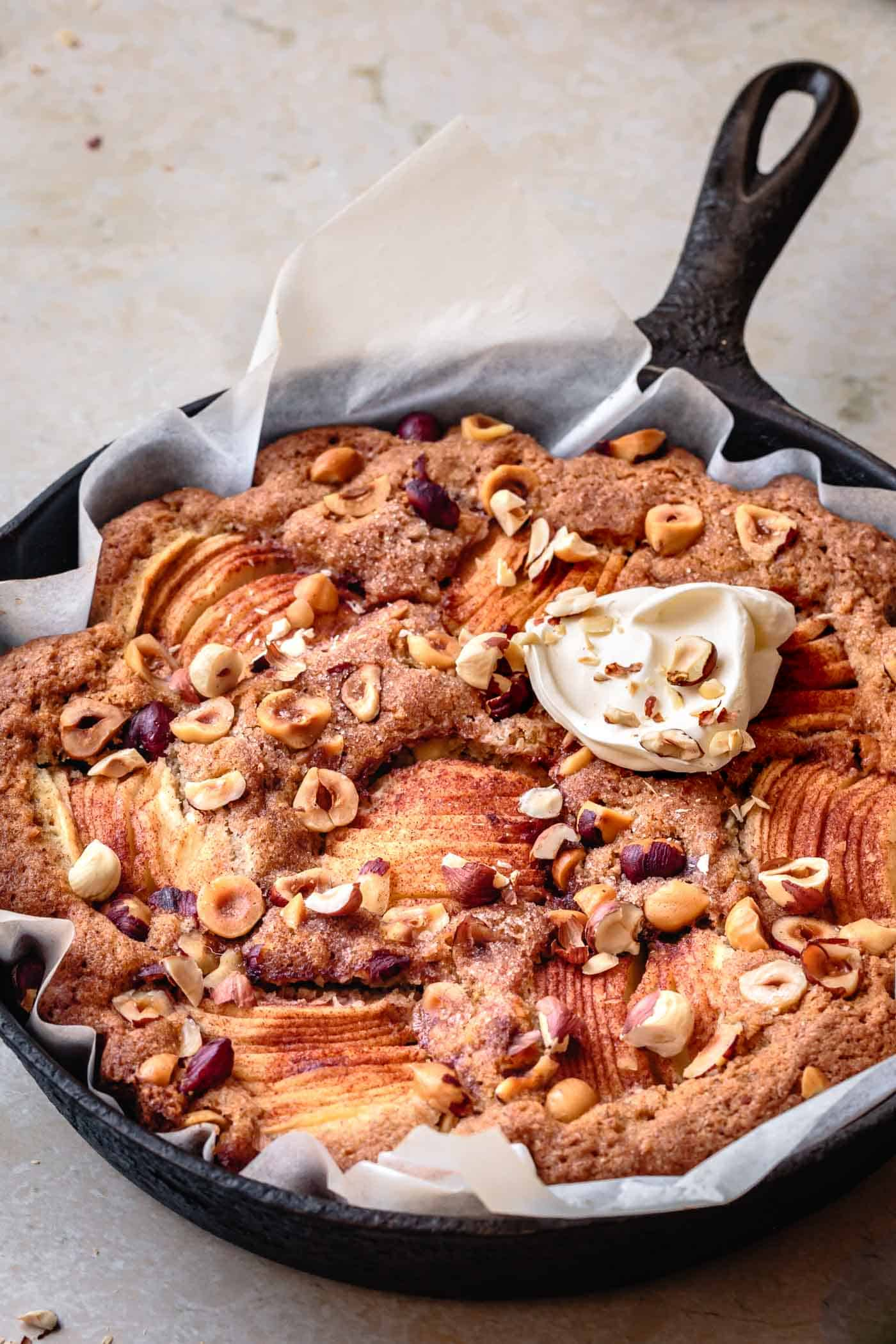 freshly baked apple hazelnut cake in a skillet topped with swirl of creme fraiche