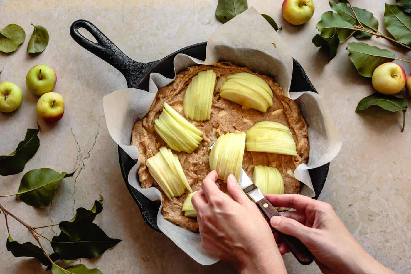 Placing apples on top of the gluten-free apple cake batter