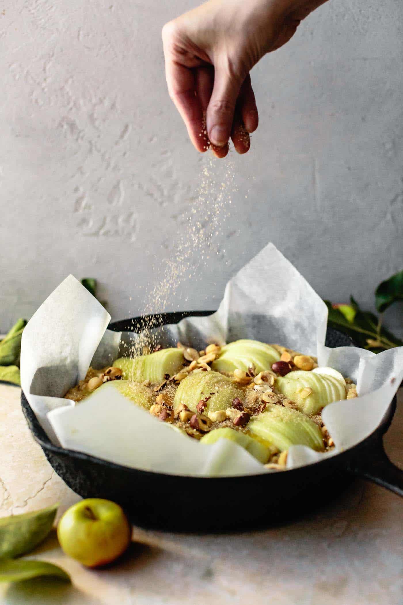 Sprinkling cinnamon sugar over gluten-free apple cake
