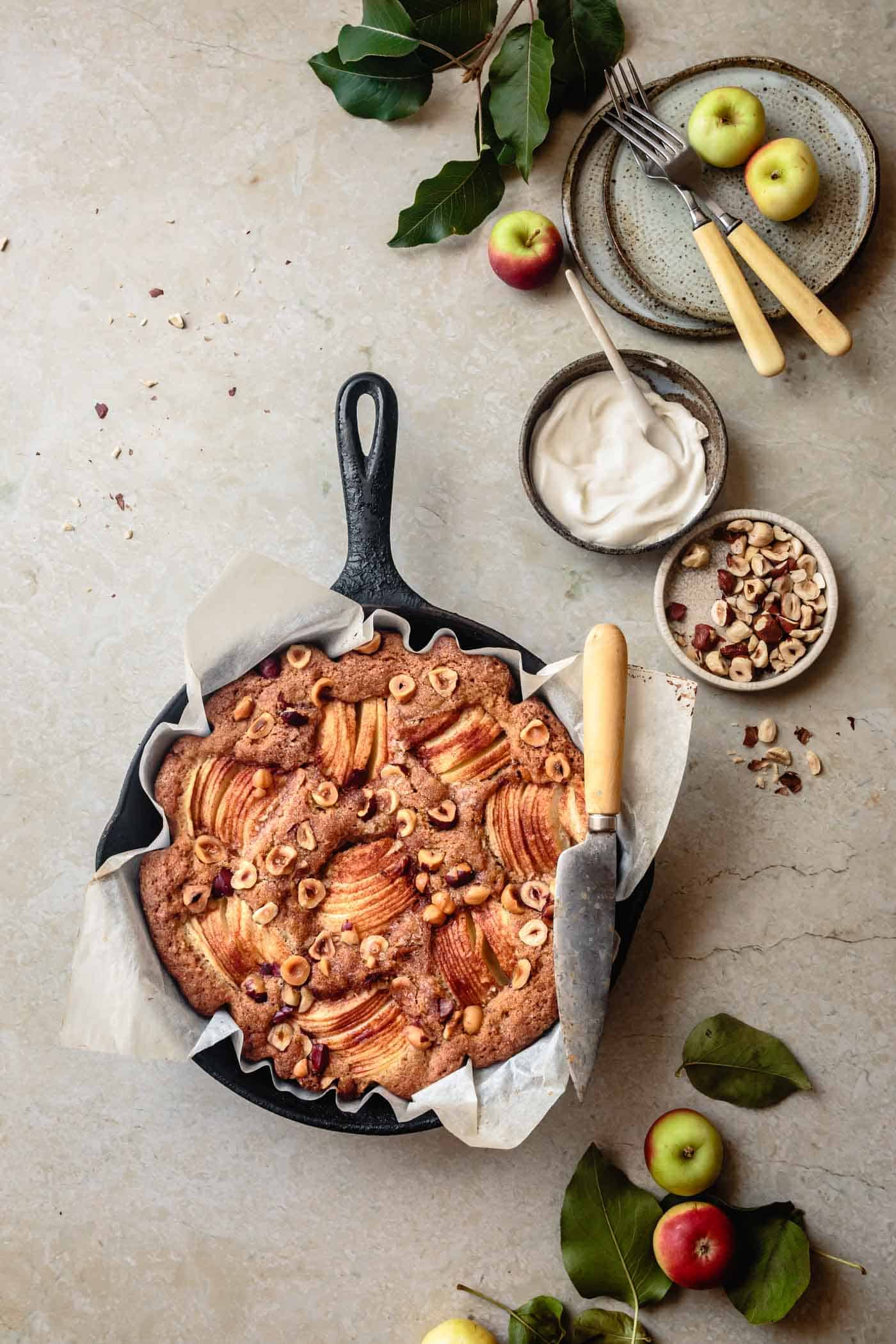 Gluten-free apple cake with brown butter and hazelnuts being served from a skillet