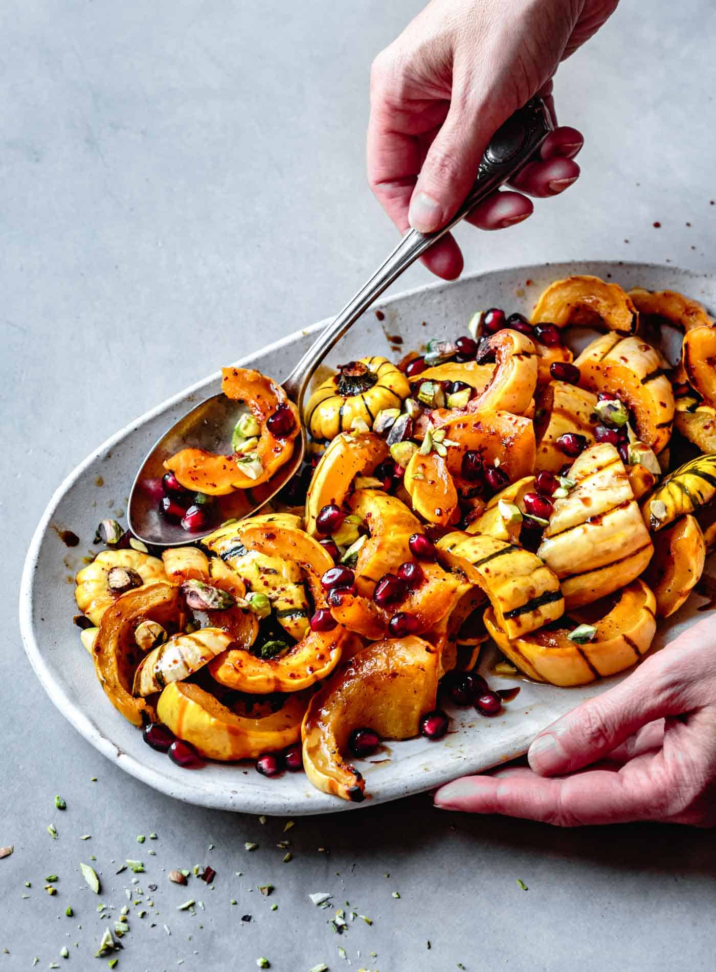 Serving roasted delicata squash with brown butter, pomegranate and pistachios