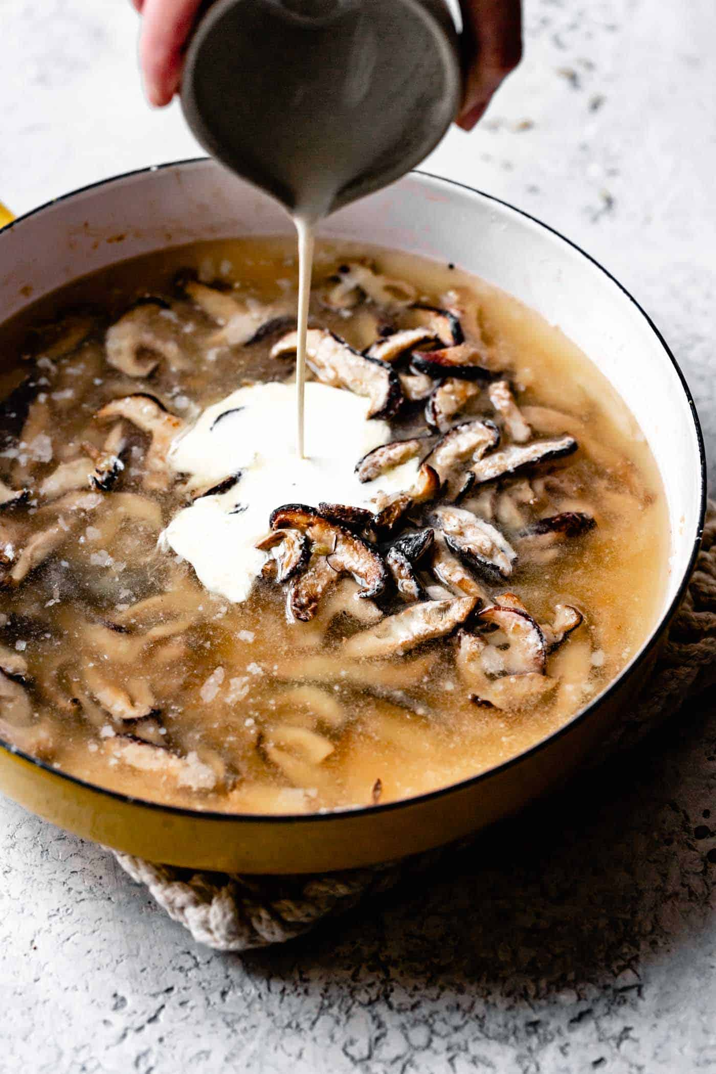 Gluten-free homemade mushroom gravy recipe: adding cream to the mushrooms and stock