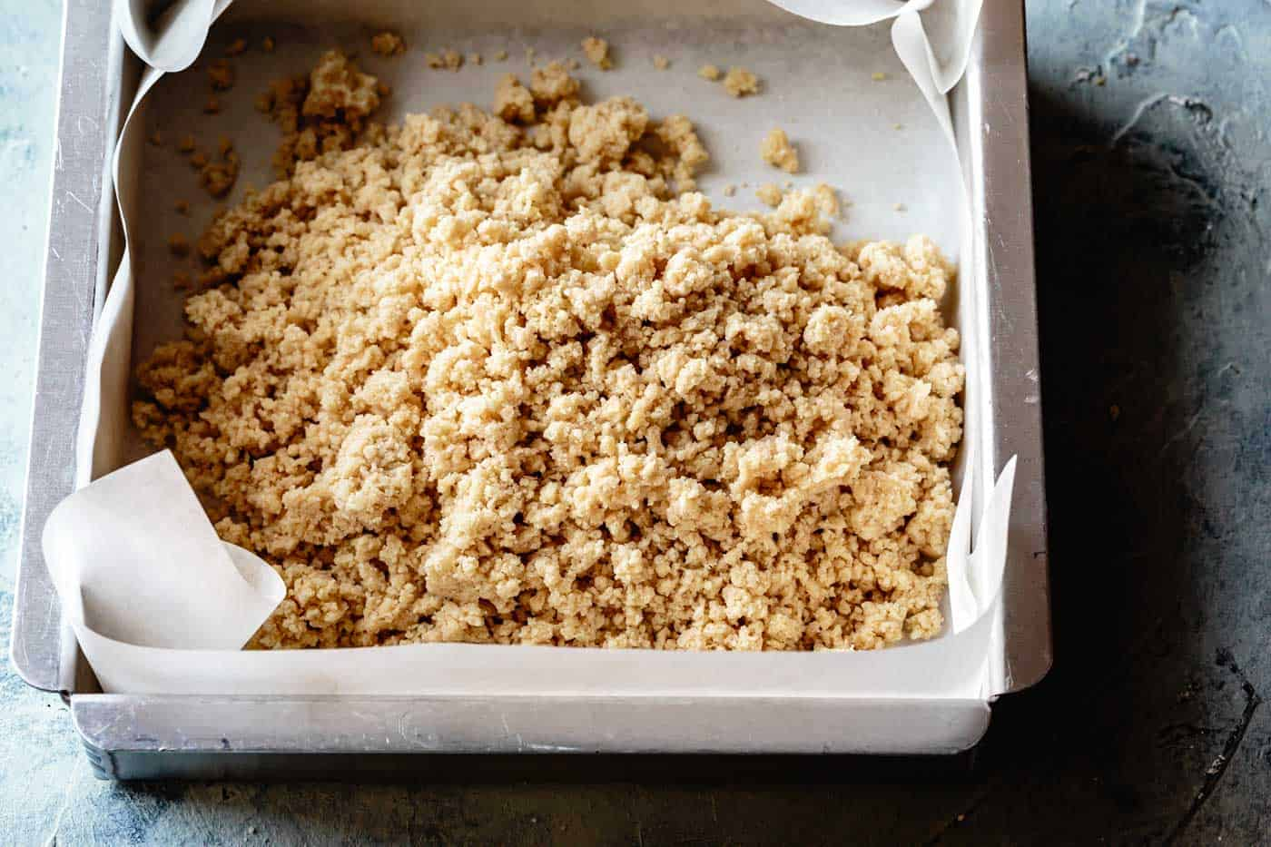 crumble dough for gluten-free shortbread crust in a pan