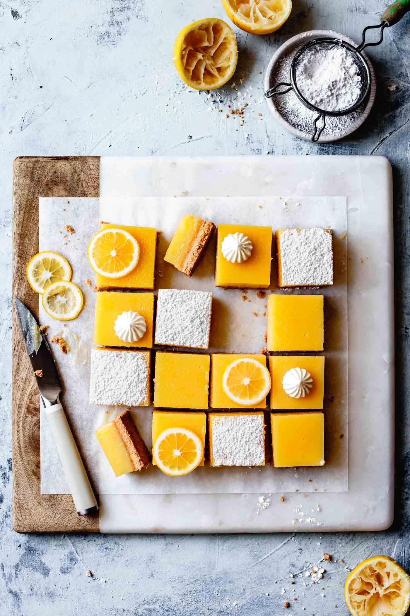 Gluten-free lemon tart or lemon bars recipe, decorated on a cutting board