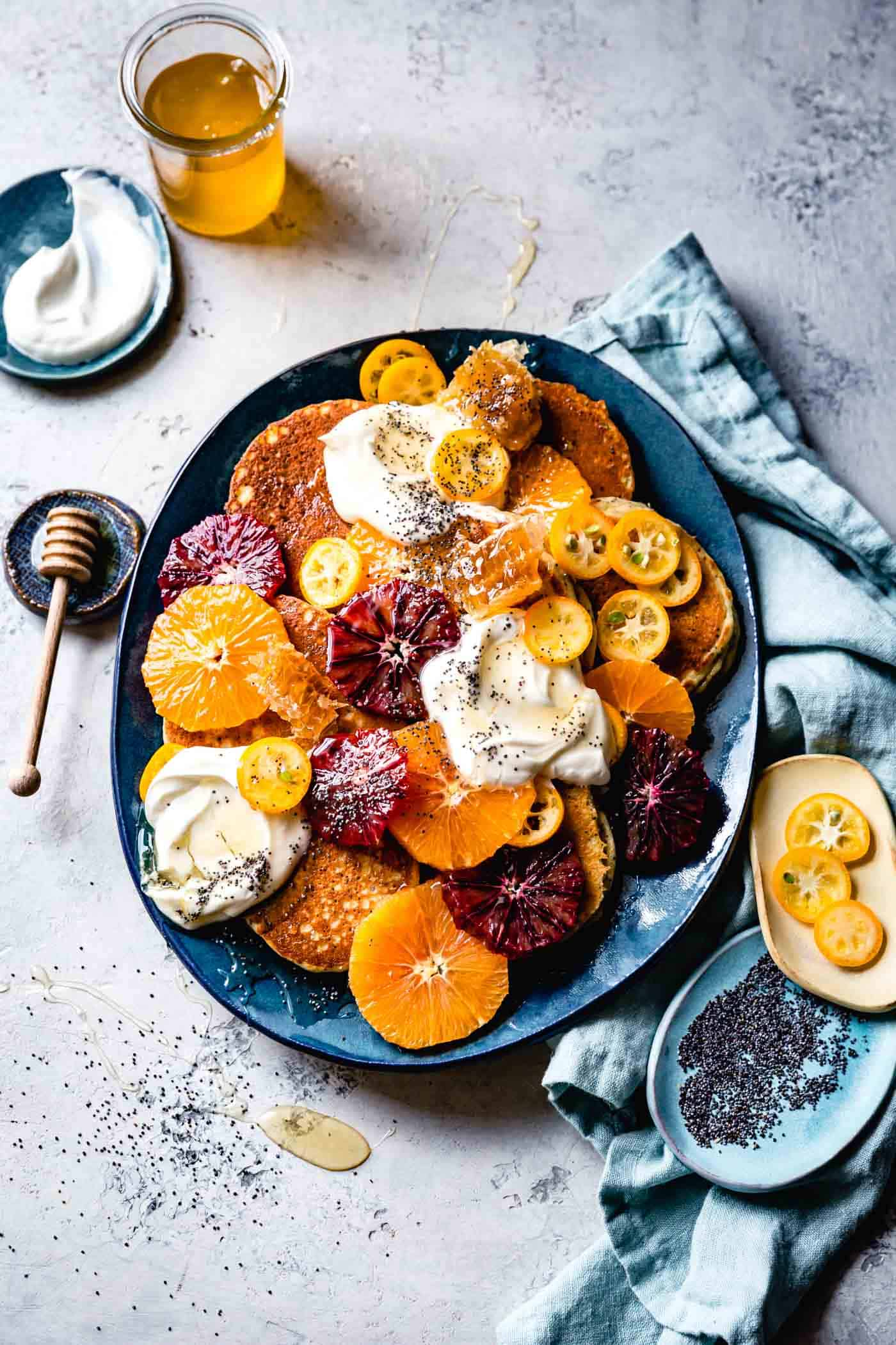 Platter of gluten-free almond flour pancakes with yogurt, citrus, honey, and poppy seeds