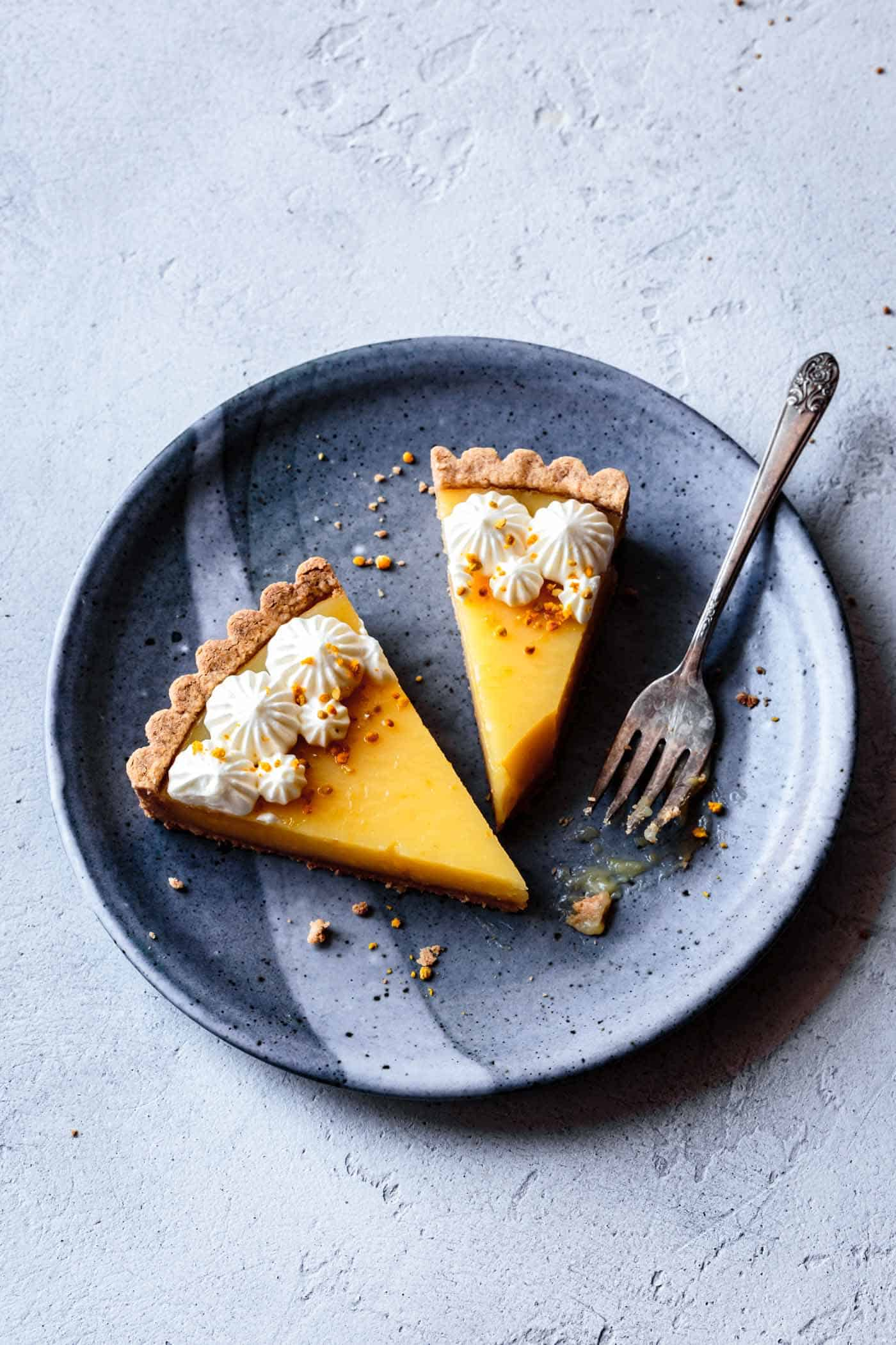 Slices of lemon curd tart recipe on a plate, overhead