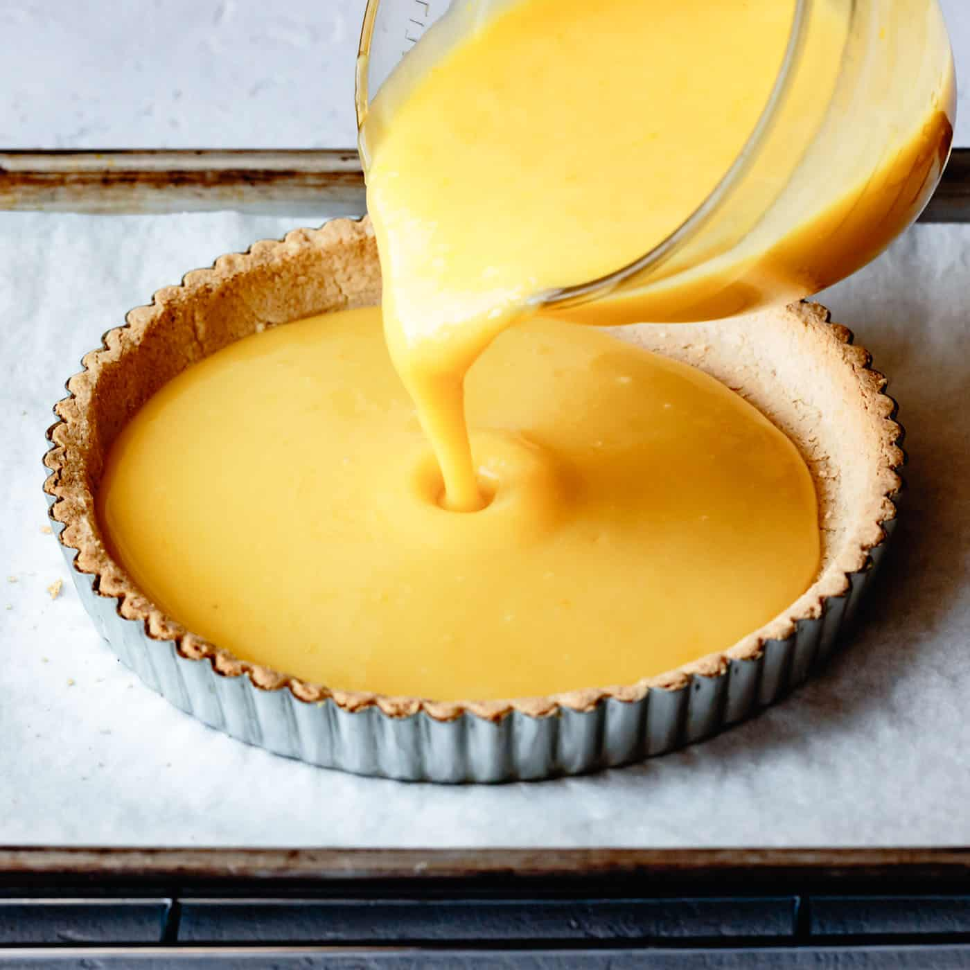 pouring lemon curd into a tart crust for lemon curd tart