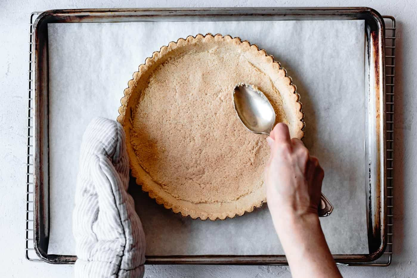 pressing gluten-free tart crust with a spoon to compress the crumb