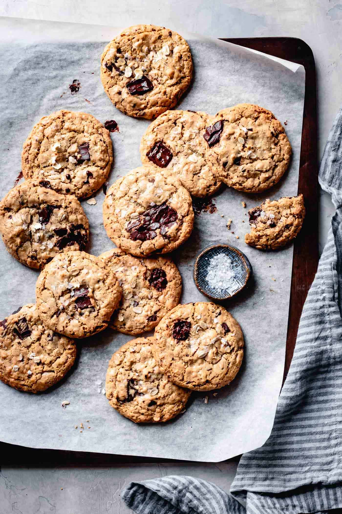 A baking sheet full of vegan gluten-free oatmeal chocolate chip cookies fresh from the oven
