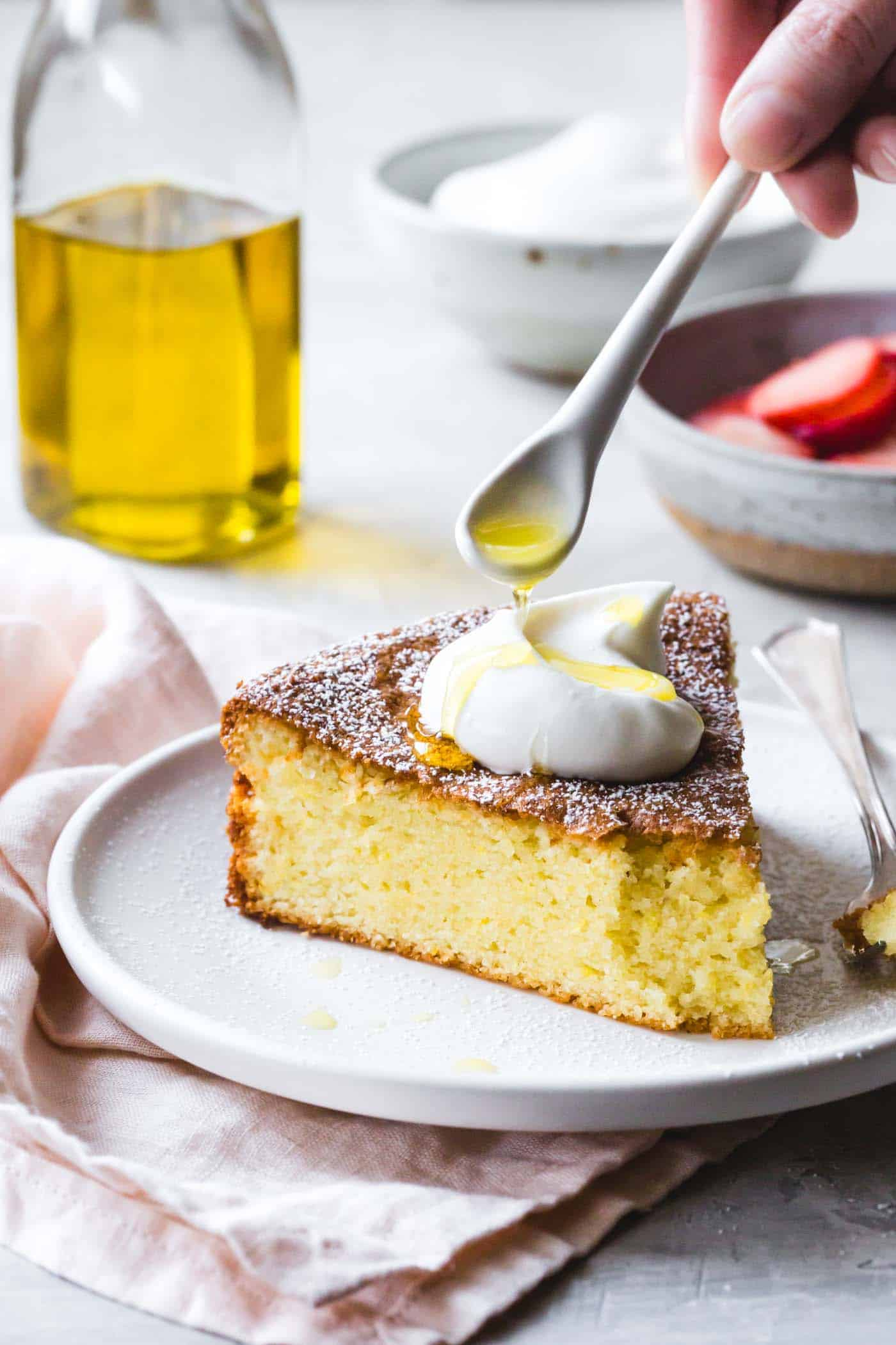 Drizzling olive oil on lemon almond gluten-free olive oil cake