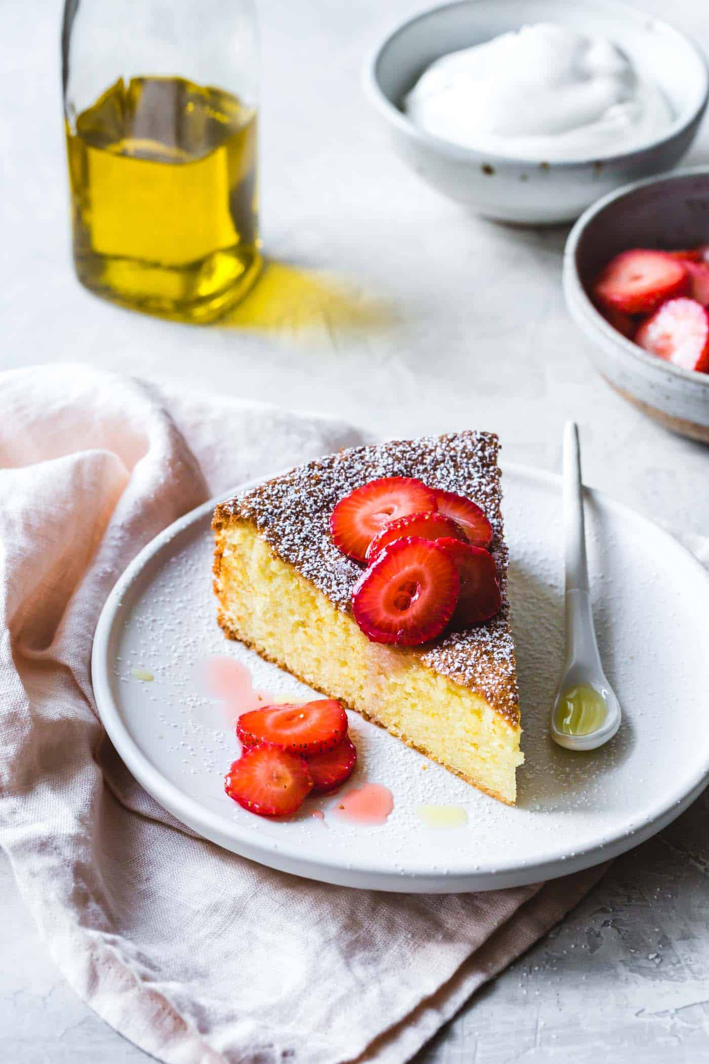 Gluten-free almond cake with lemon and olive oil, on a plate with strawberries