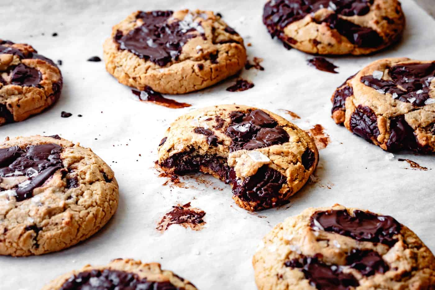 paleo grain-free chocolate chip cookies on a cookie sheet with a bite taken out