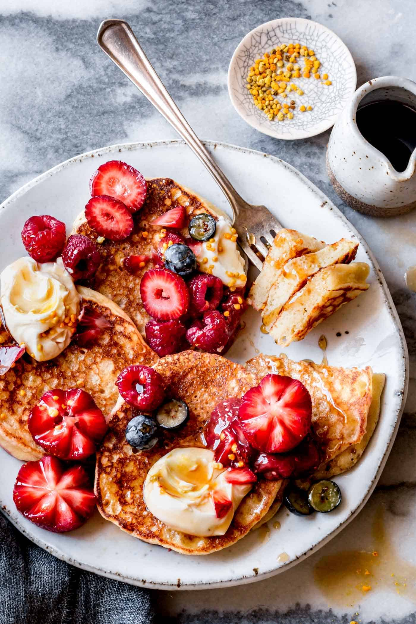 gluten-free lemon ricotta pancakes recipe on a plate with berries and syrup
