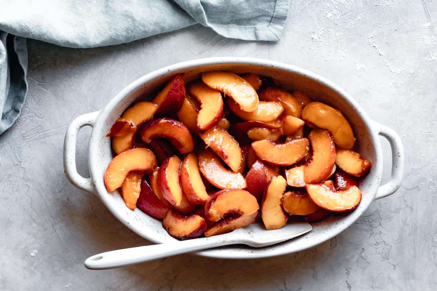 peaches in a baking pan for paleo vegan peach cobbler