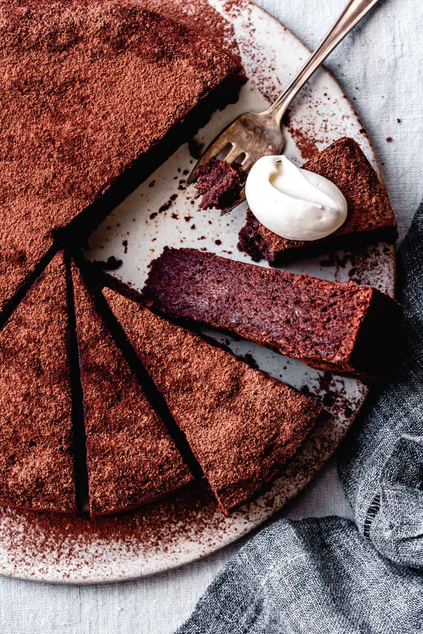 almond flour chocolate cake recipe, sliced on a serving board with whipped cream