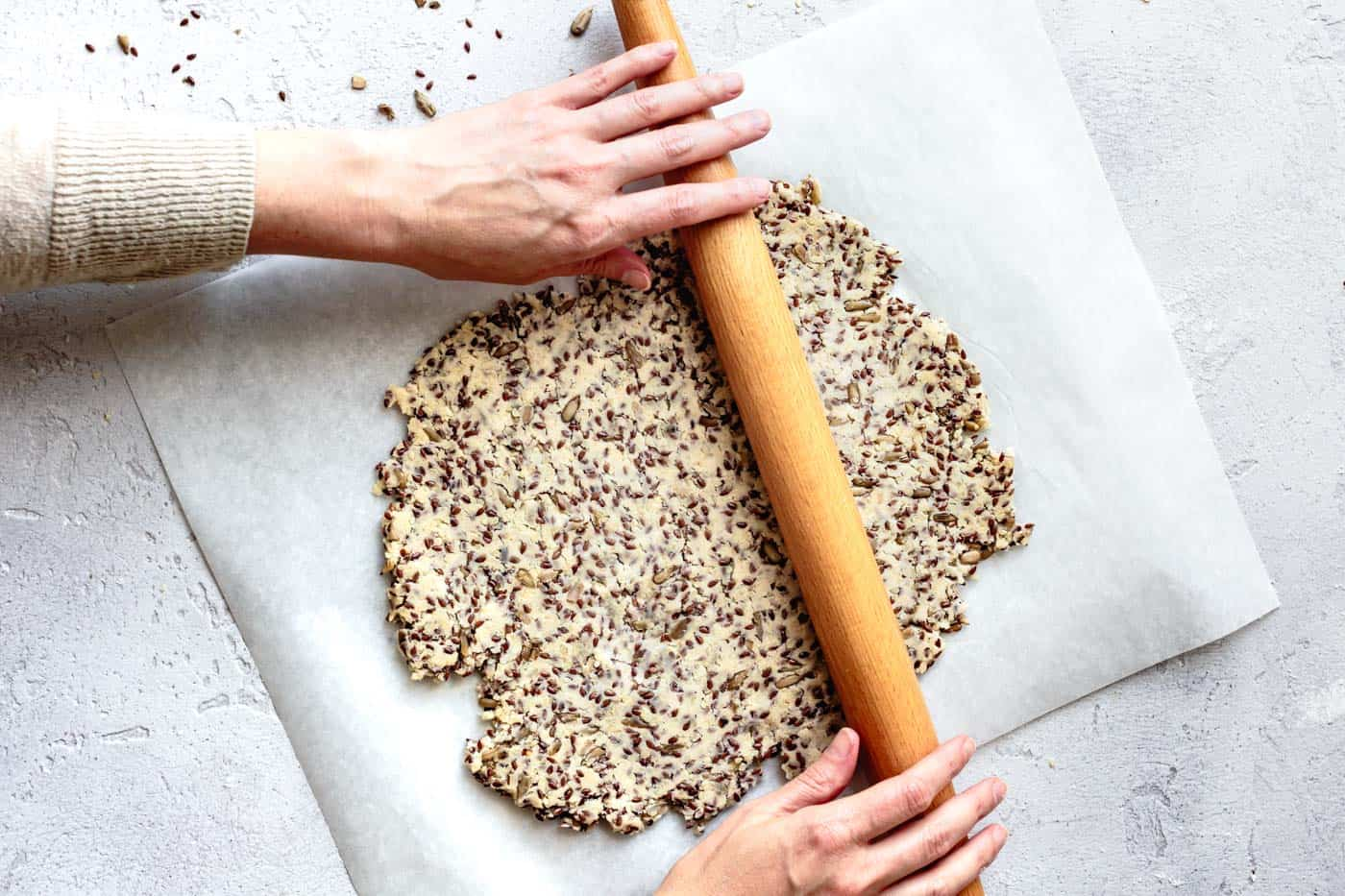 rolling the gluten-free crackers on a piece of parchment paper