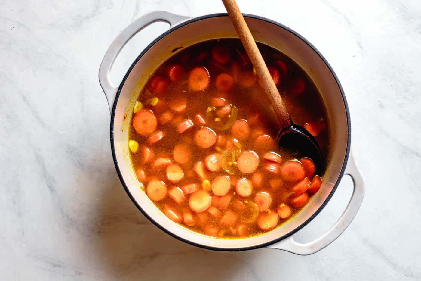 adding stock to recipe for carrot soup with ginger and coconut milk