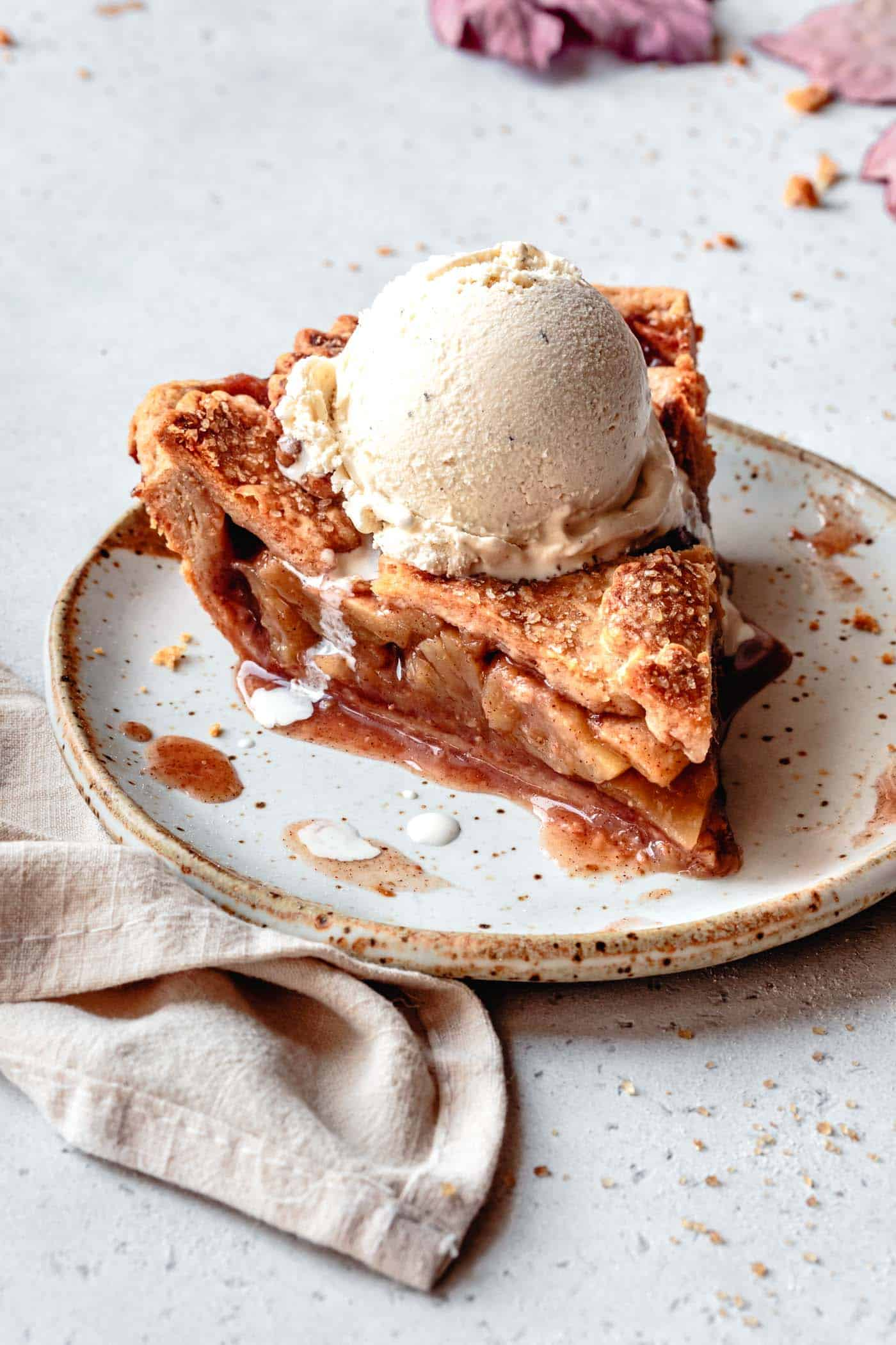 slice of gf apple pie on a beige plate with a scoop of ice cream melting on top