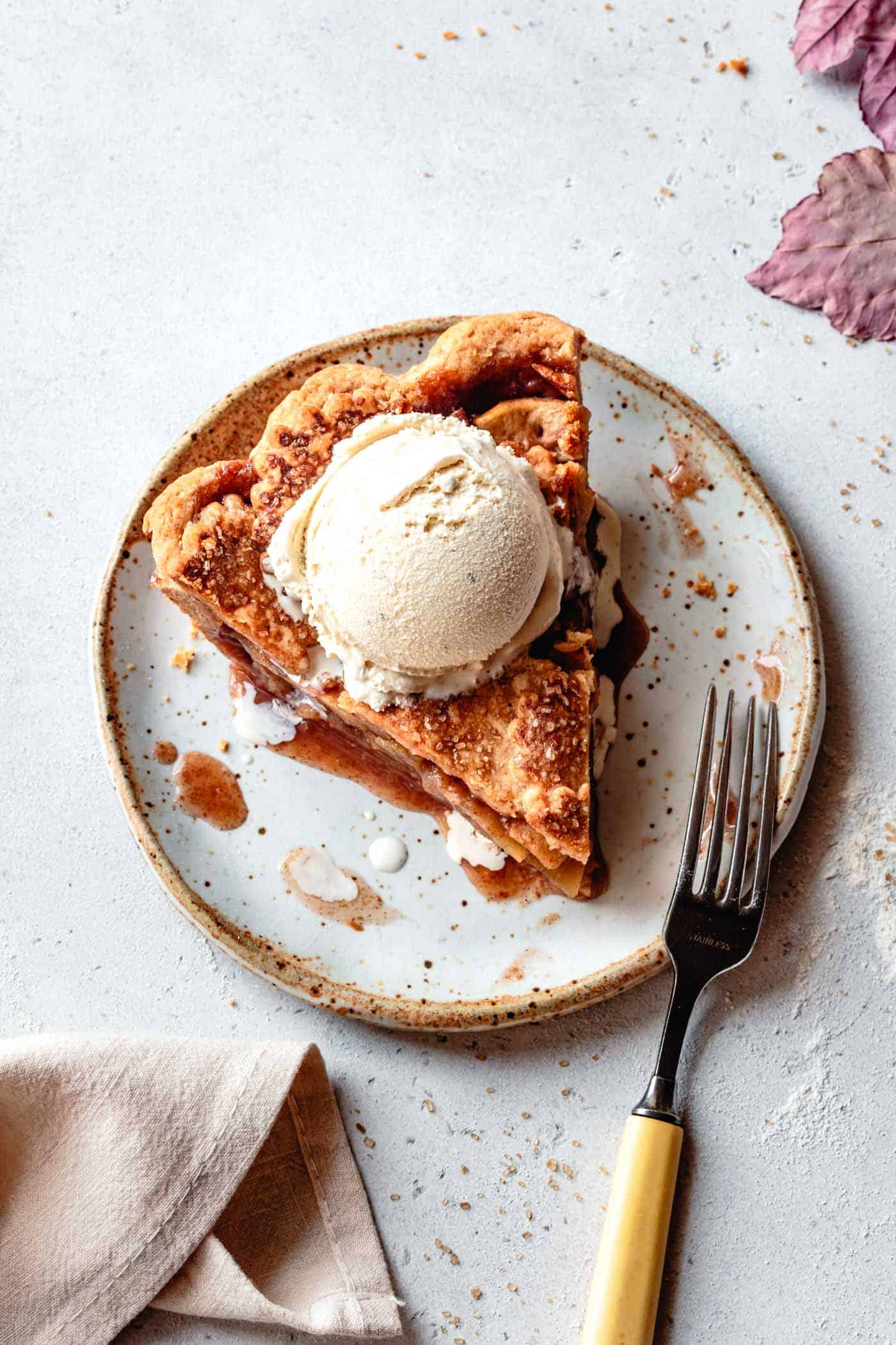a slice of gluten-free apple pie on a plate with ice cream
