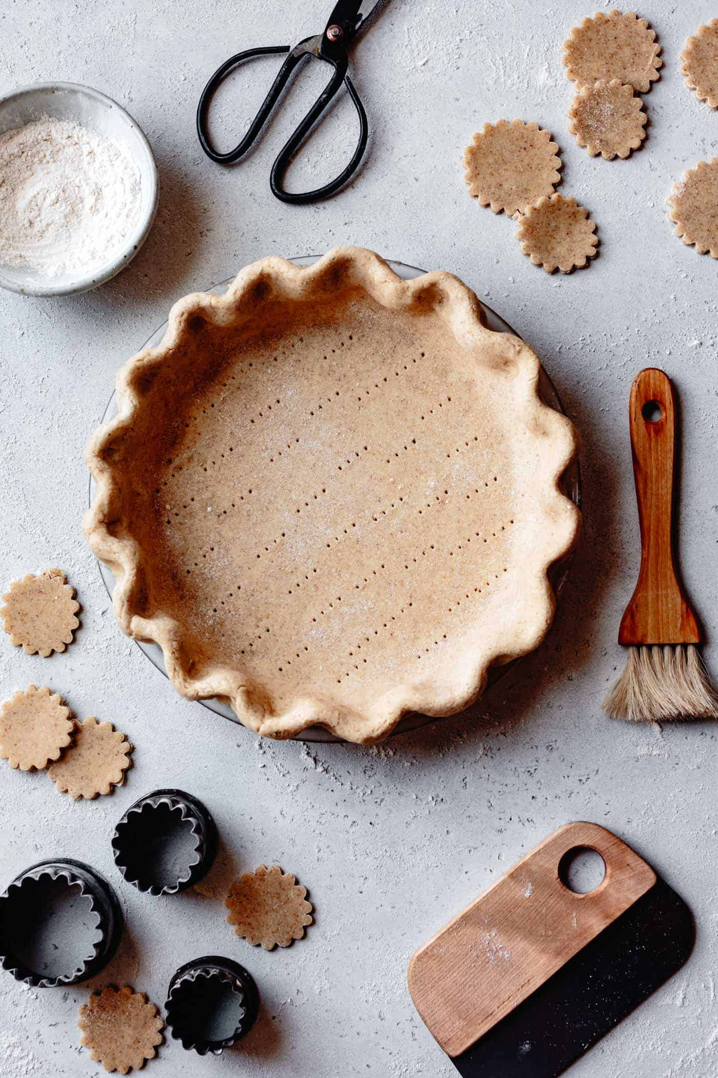 overhead of unbaked pie crust with tools on a gray speckled surface