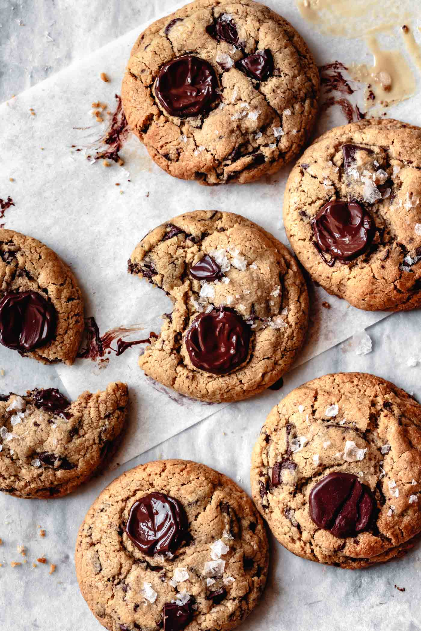 six gooey salted tahini chocolate chip cookies on parchment paper