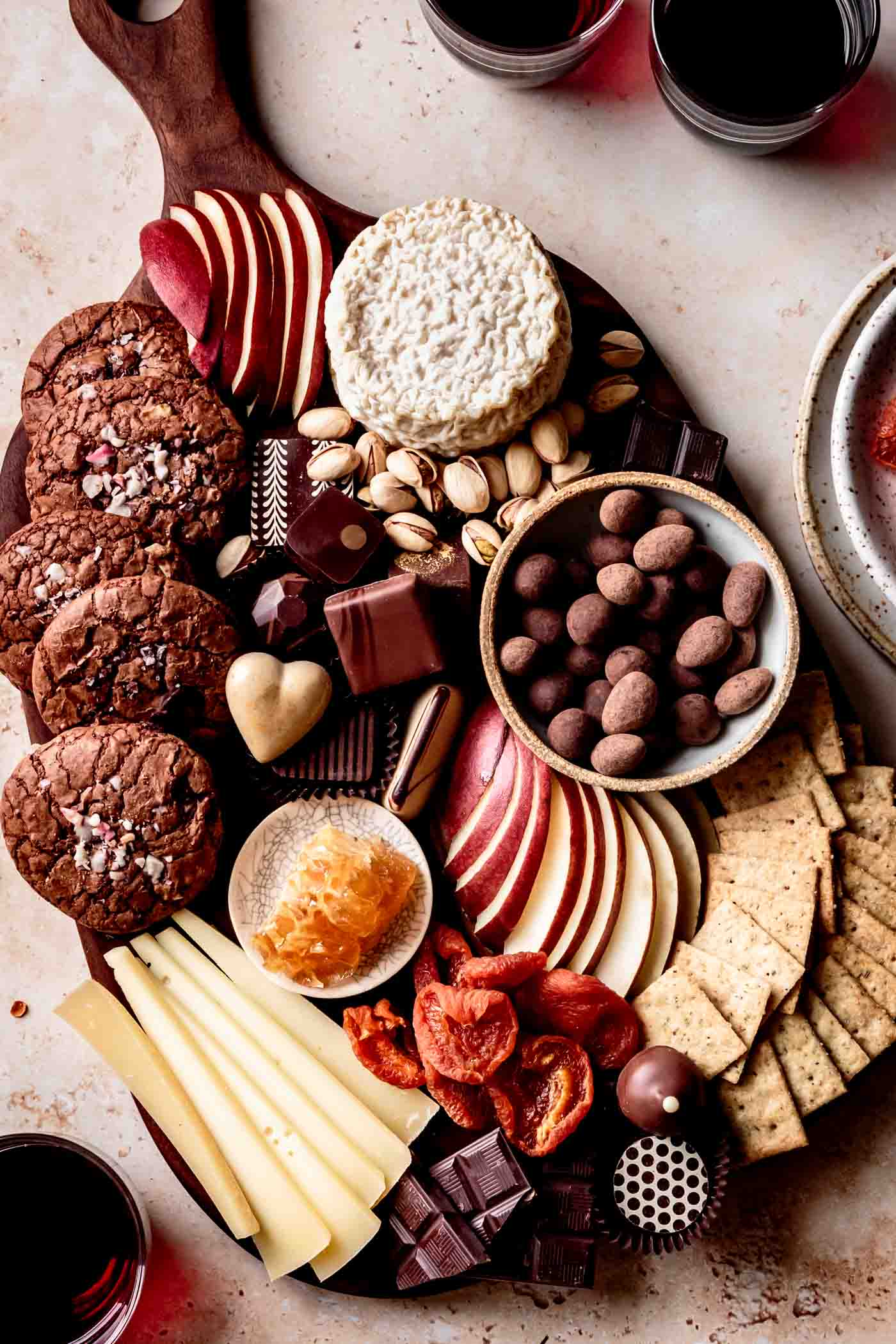 Cheese and chocolate board overhead with red wine in glasses on sandstone surface
