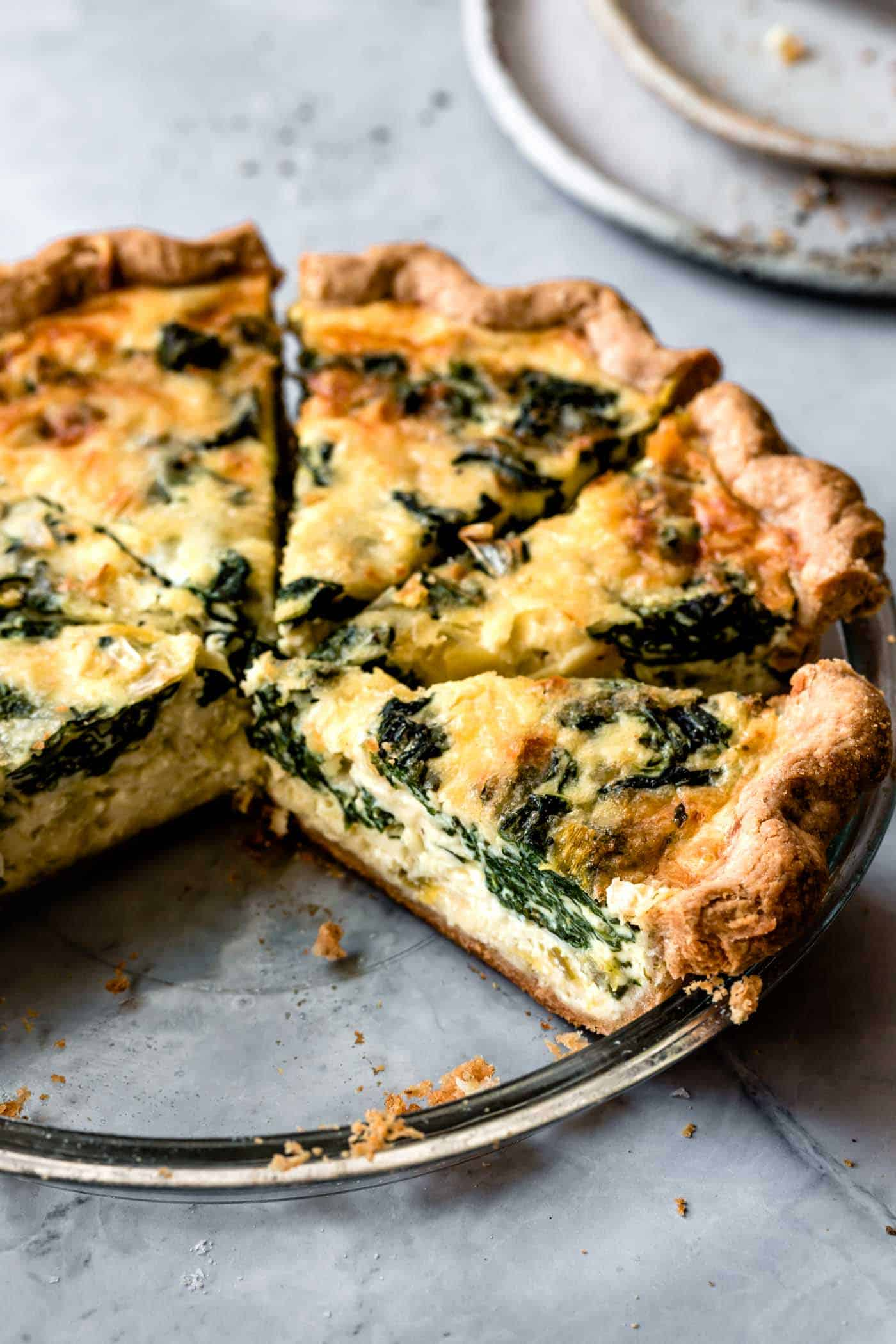 sliced spinach quiche with gluten-free quiche crust in pan