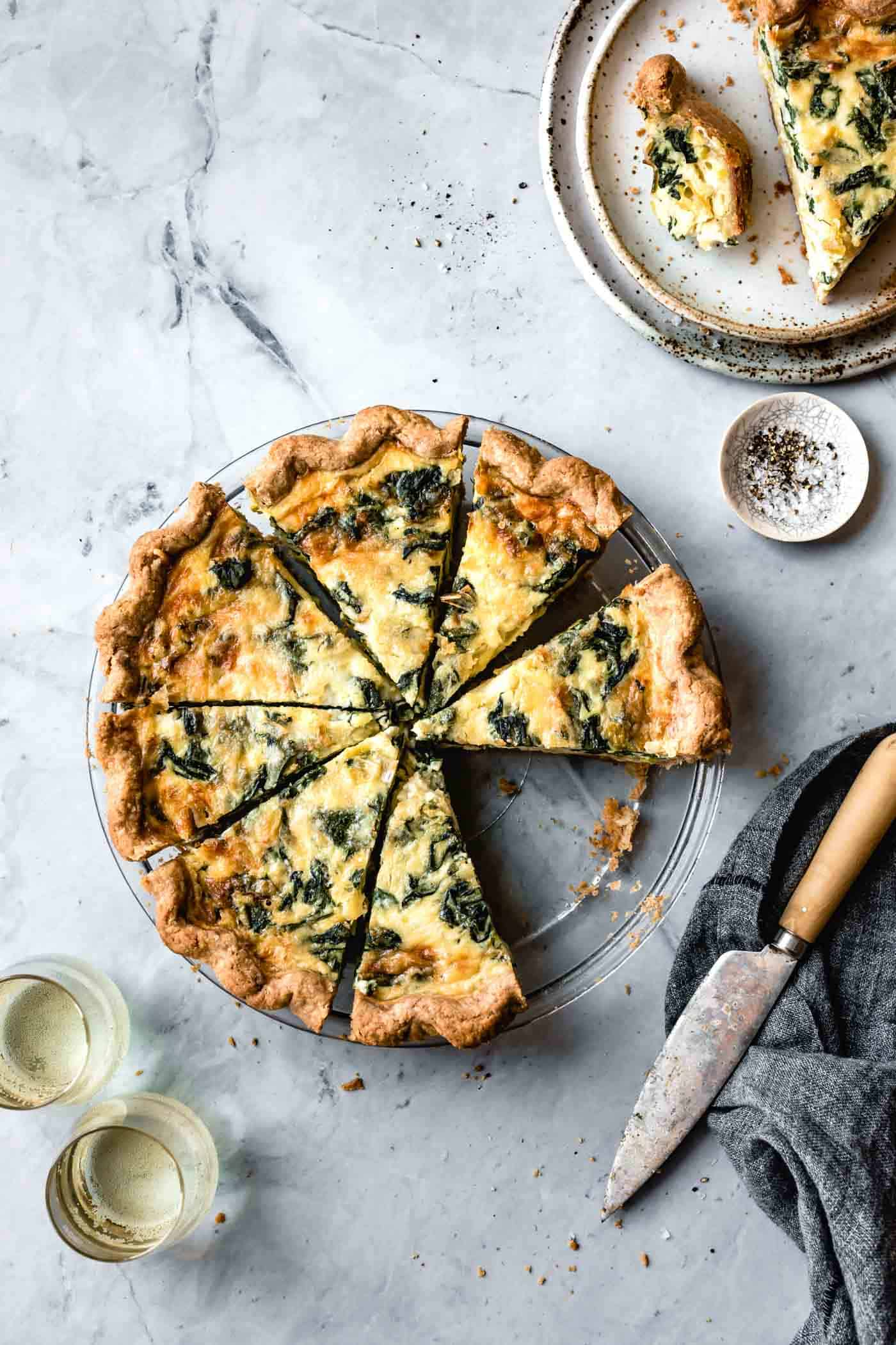 overhead of sliced spinach and leek quiche recipe on marble surface with white wine, plates, and utensils