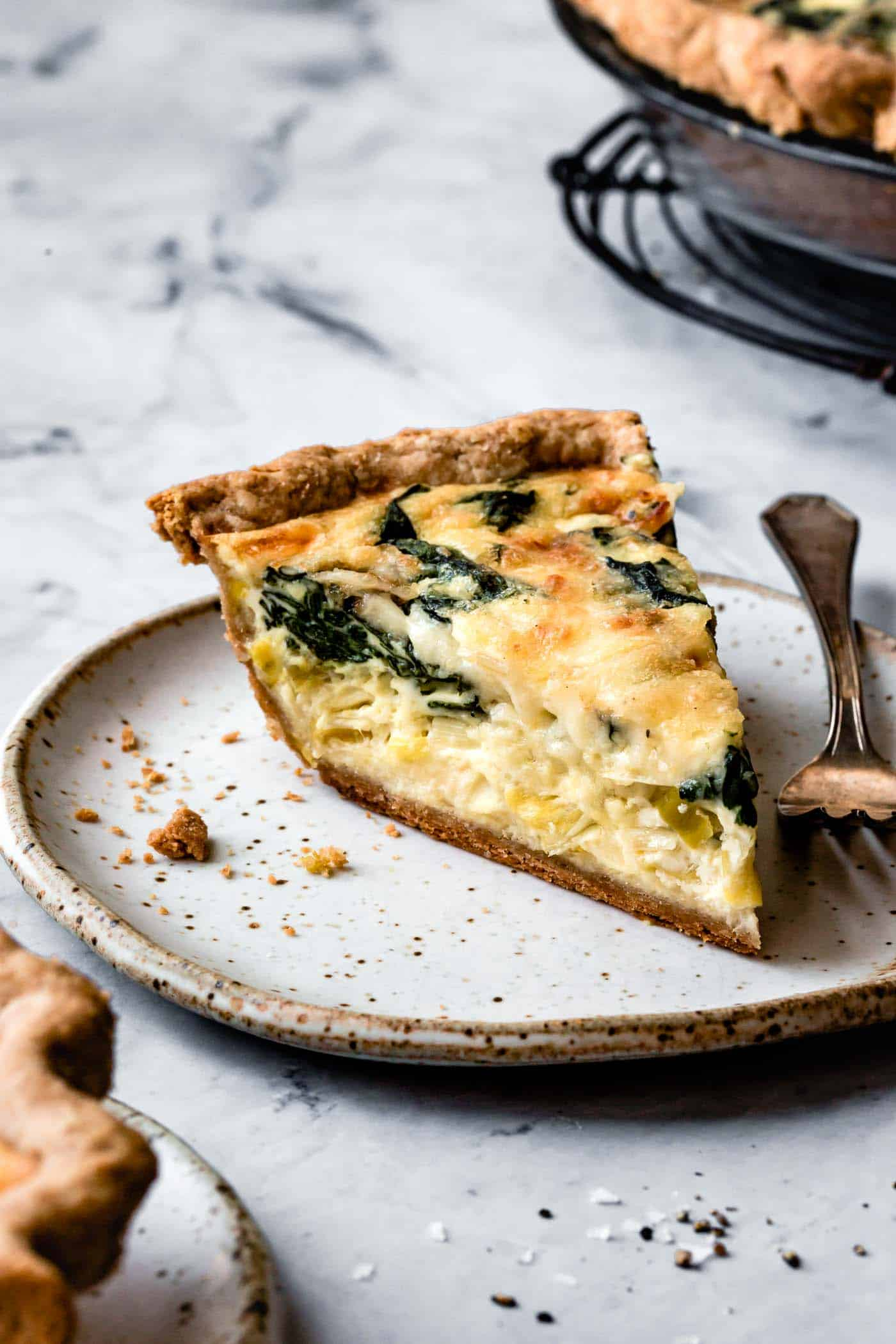 slice of spinach and cheese quiche, side angle