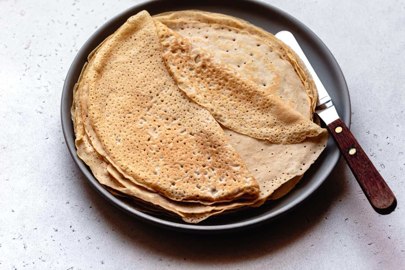 dairy-free almond milk crepes stacked on a plate