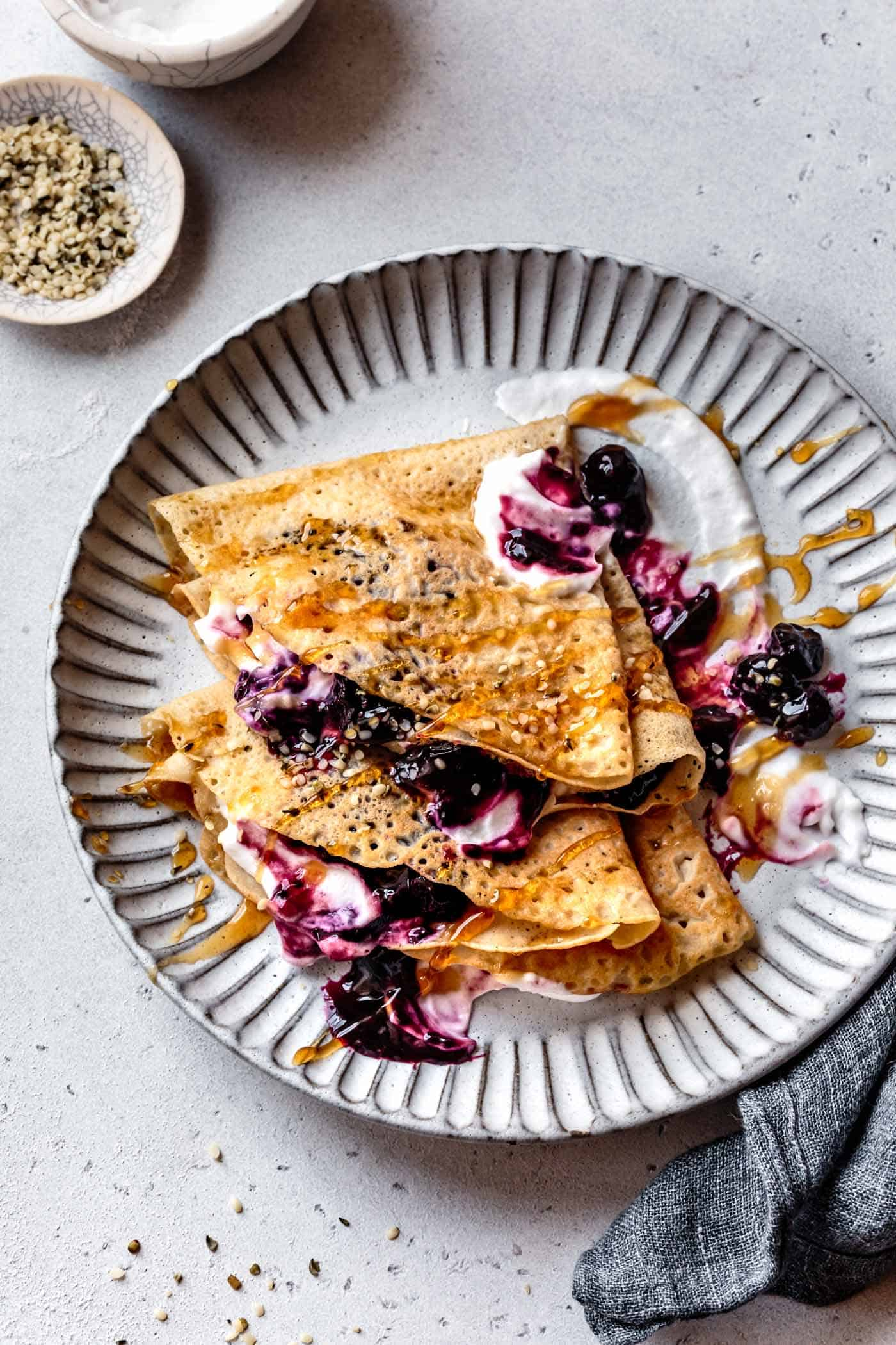 healthy crepes on a plate with berries and yogurt