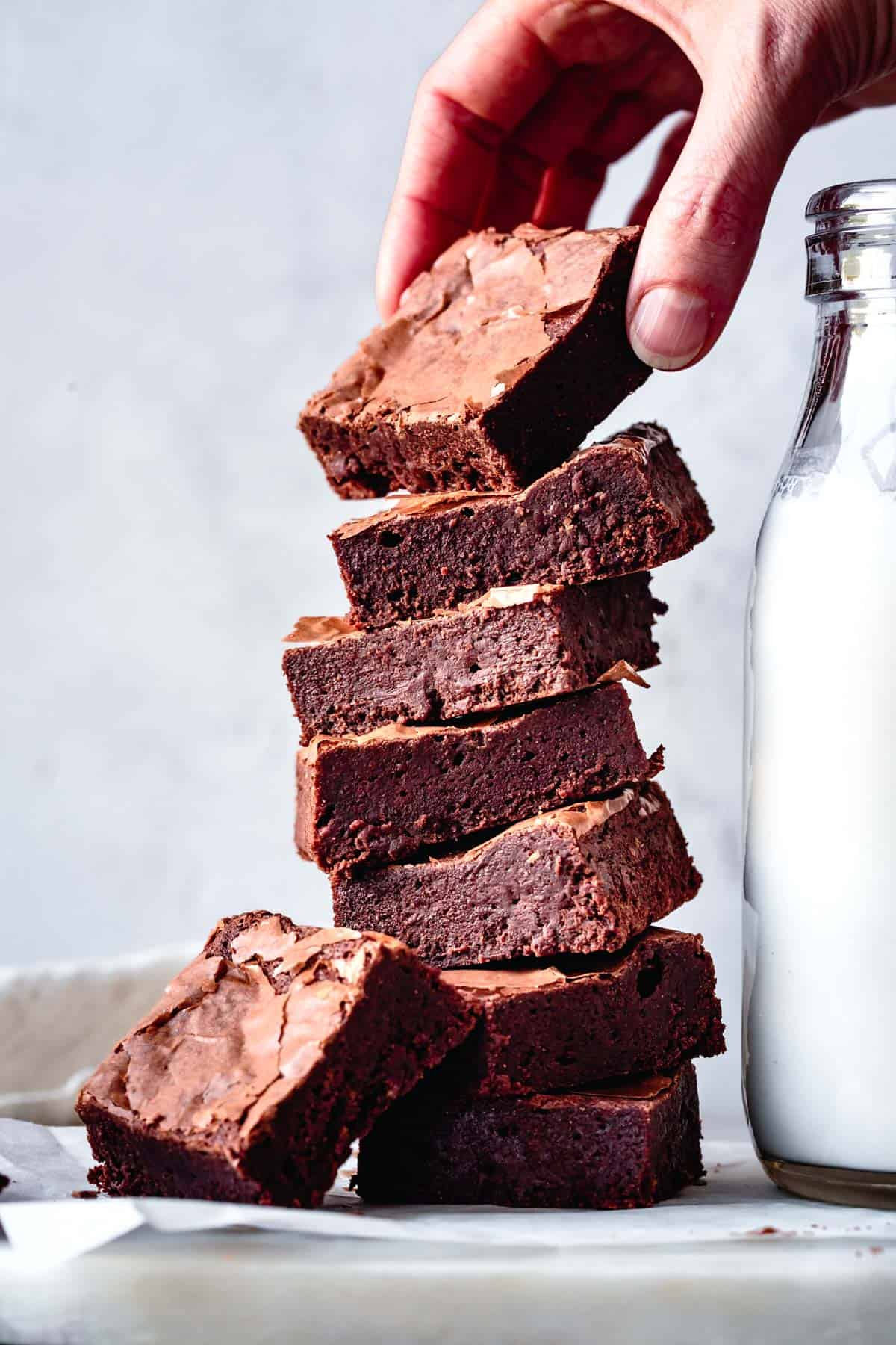 Stack of gluten-free brownies with a hand lifting the top brownie