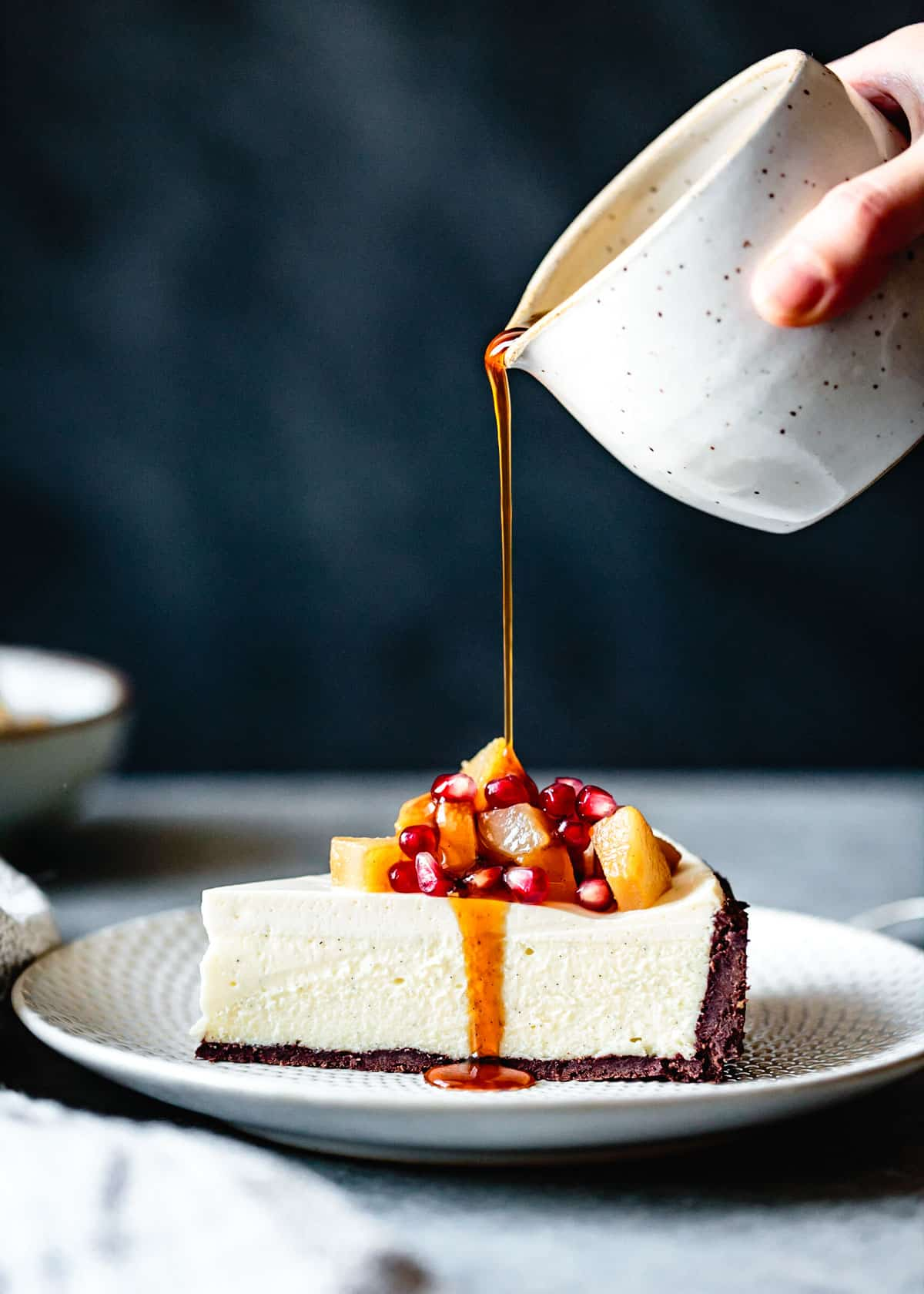 slice of cheesecake topped with poached pears and pomegranate being drizzled with caramel