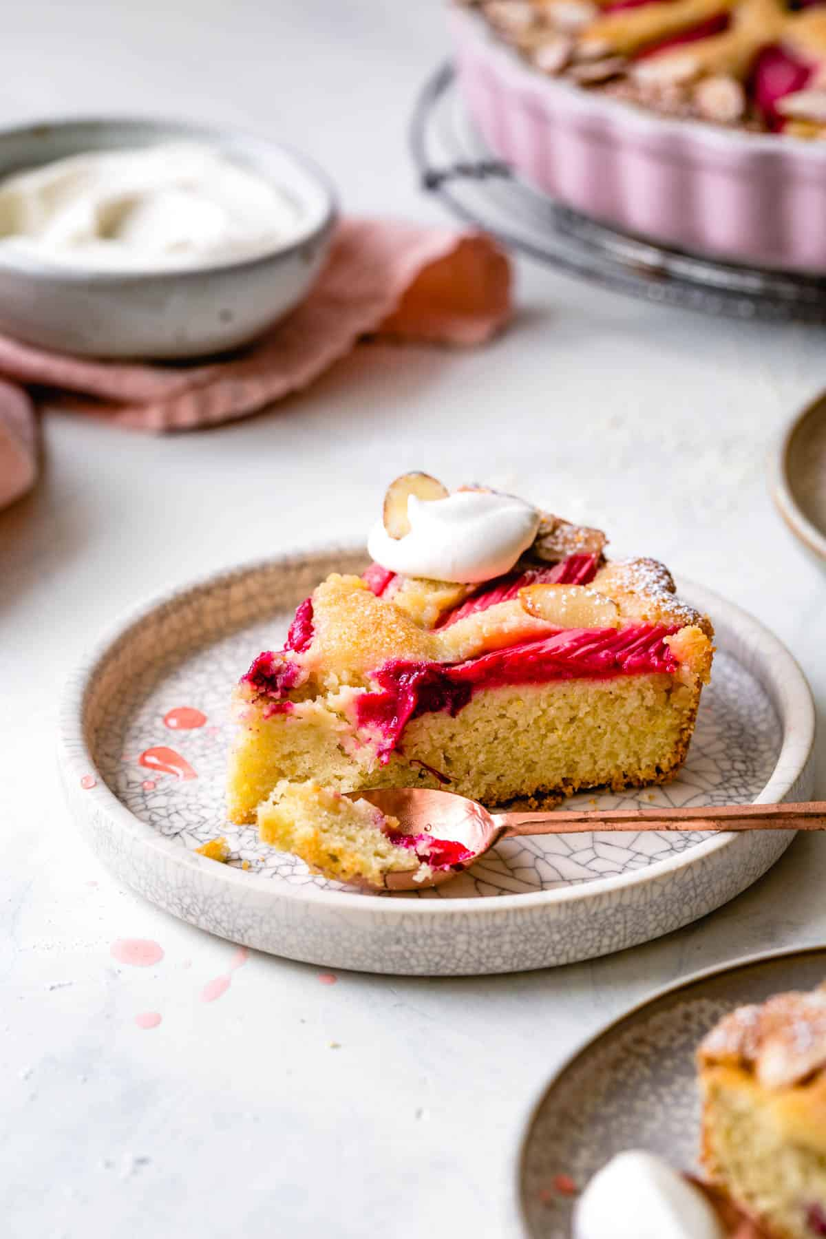 rhubarb cake on a crackled plate topped with whipped cream
