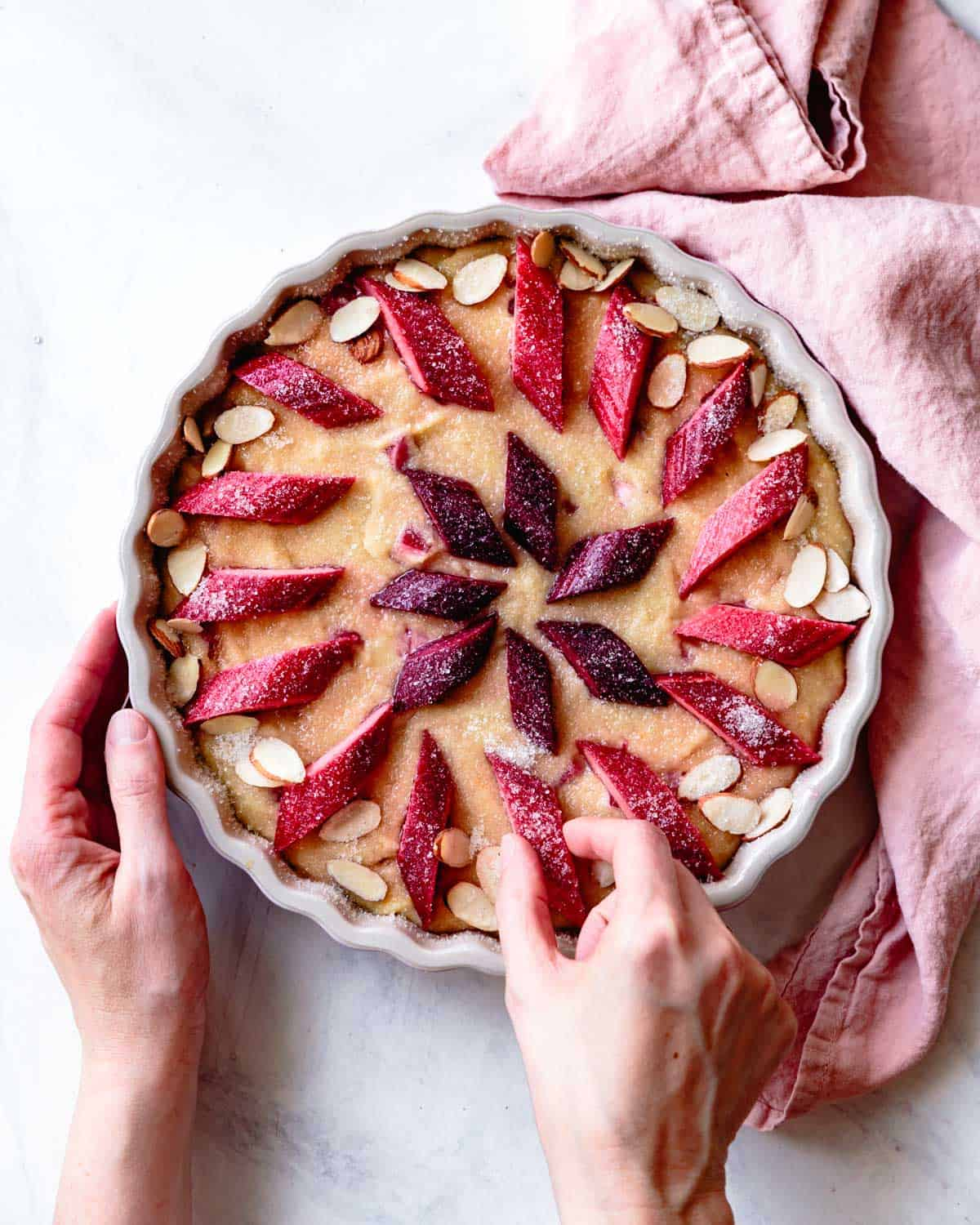 placing rhubarb slices and almonds over the cake
