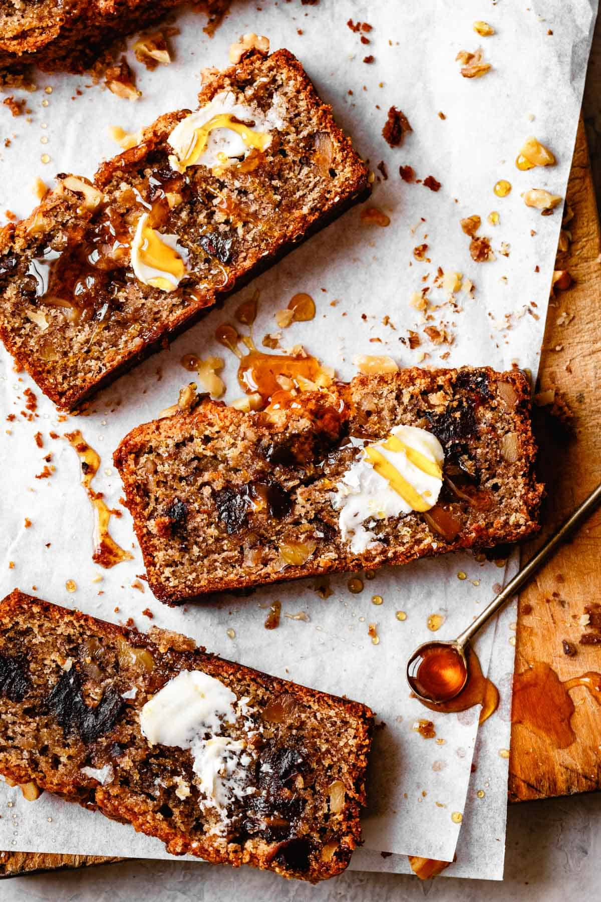 slices of banana bread on parchment with honey drizzle