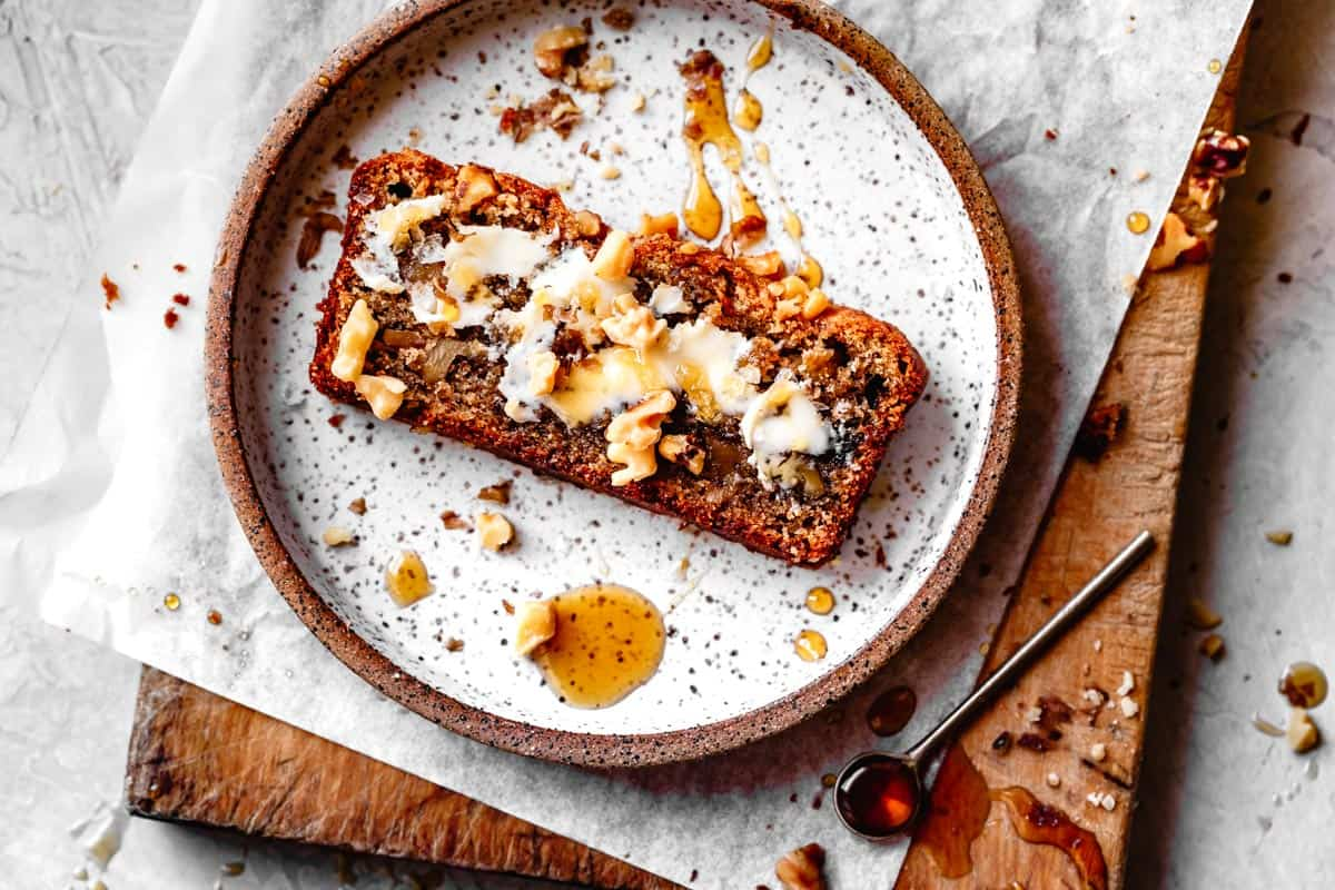 slice of healthy banana bread on a plate with butter, honey, and walnuts
