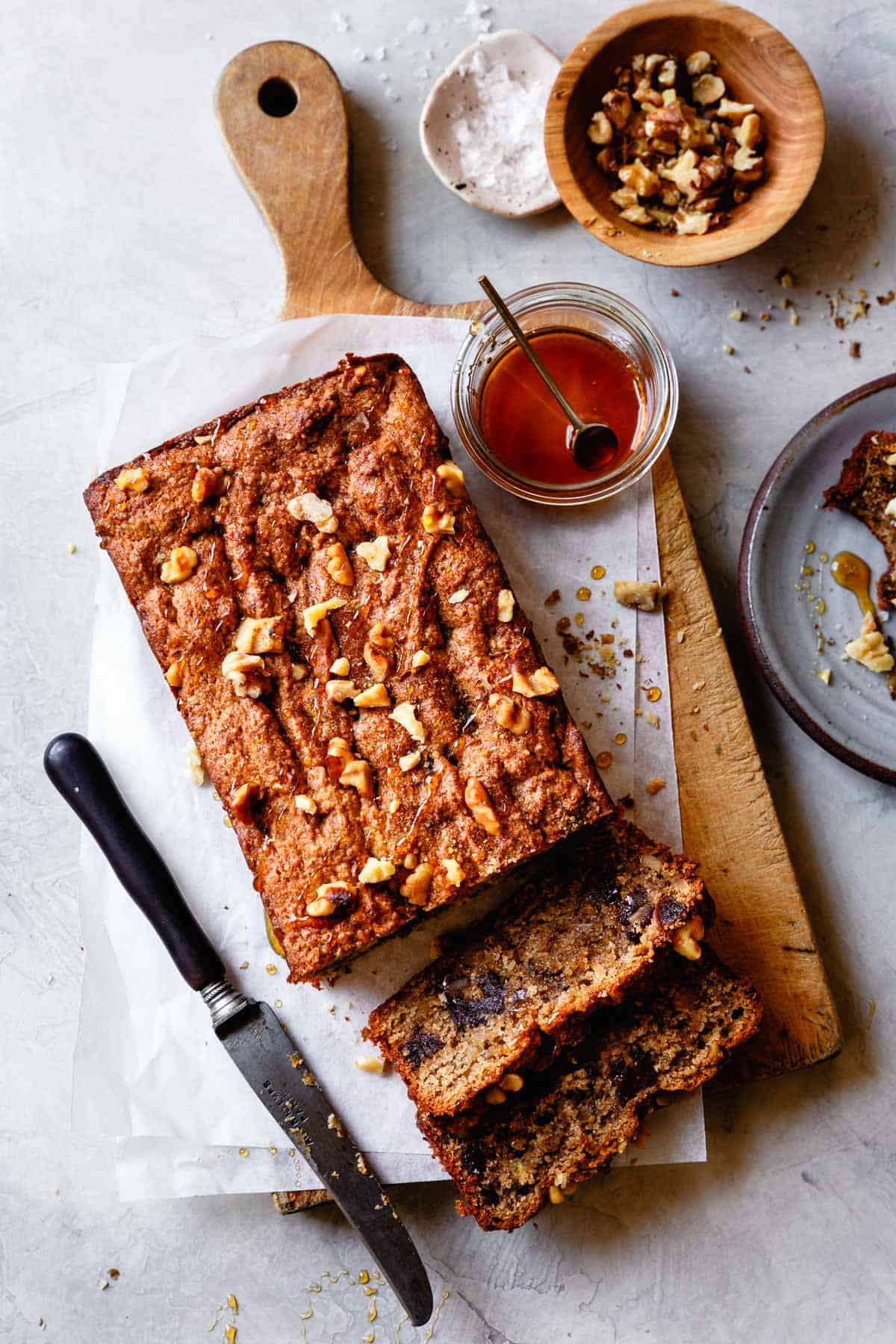 banana bread on a board with honey, nuts, and flaky salt