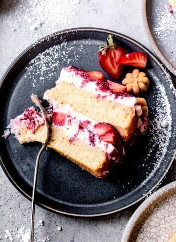close-up of slice of gluten-free strawberry cake on a plate with powdered sugar