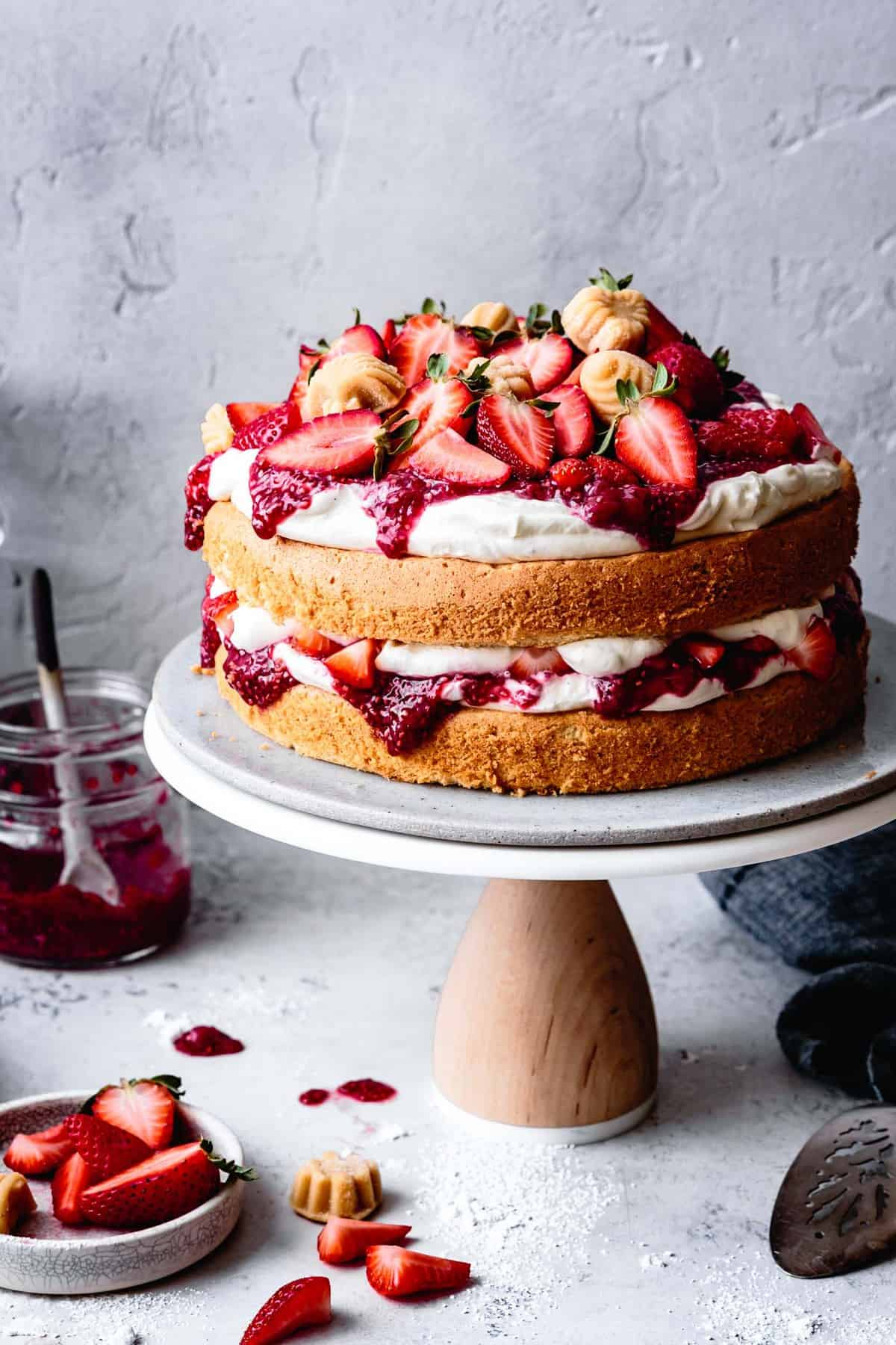 gluten-free sponge cake layered with strawberries, cream, and jam on a cake stand