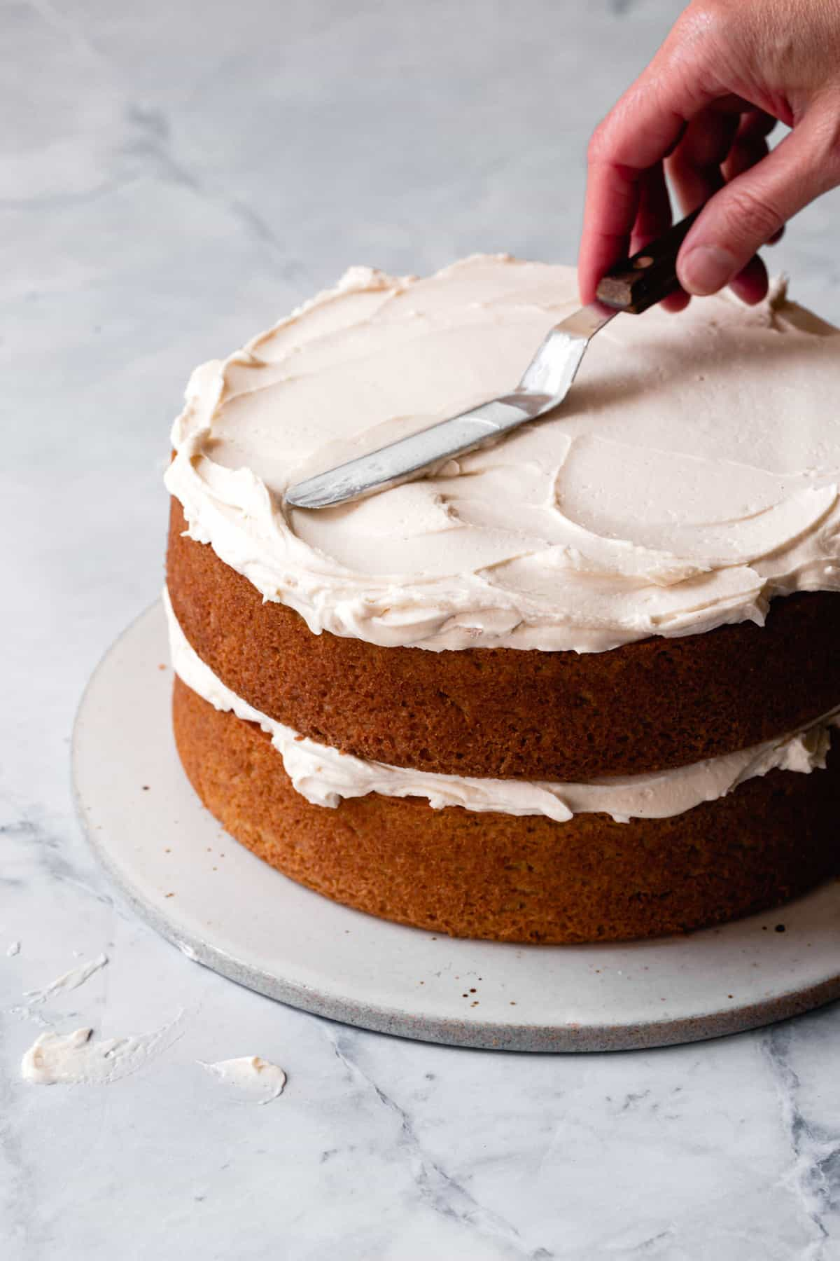 paleo icing being spread on a layer cake