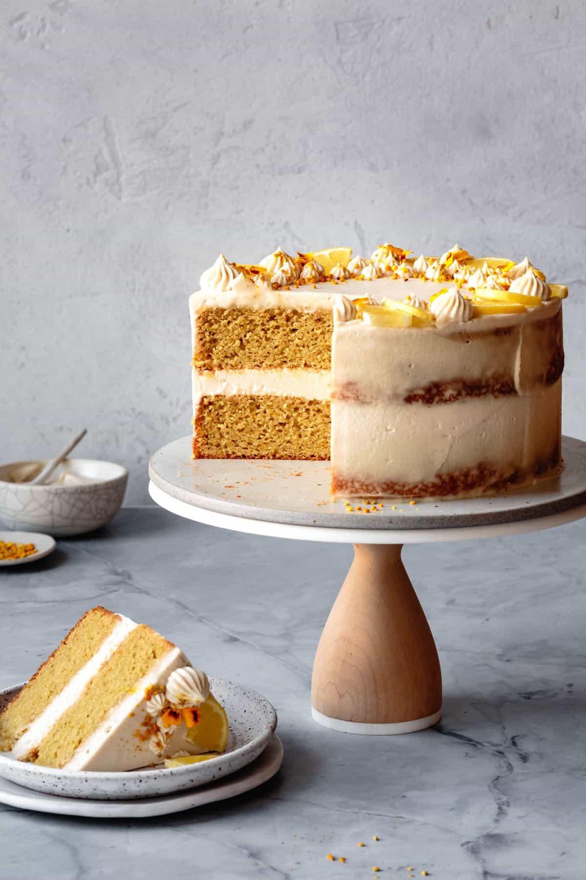 paleo lemon cake with a slice cut out on a cake stand against a plaster wall
