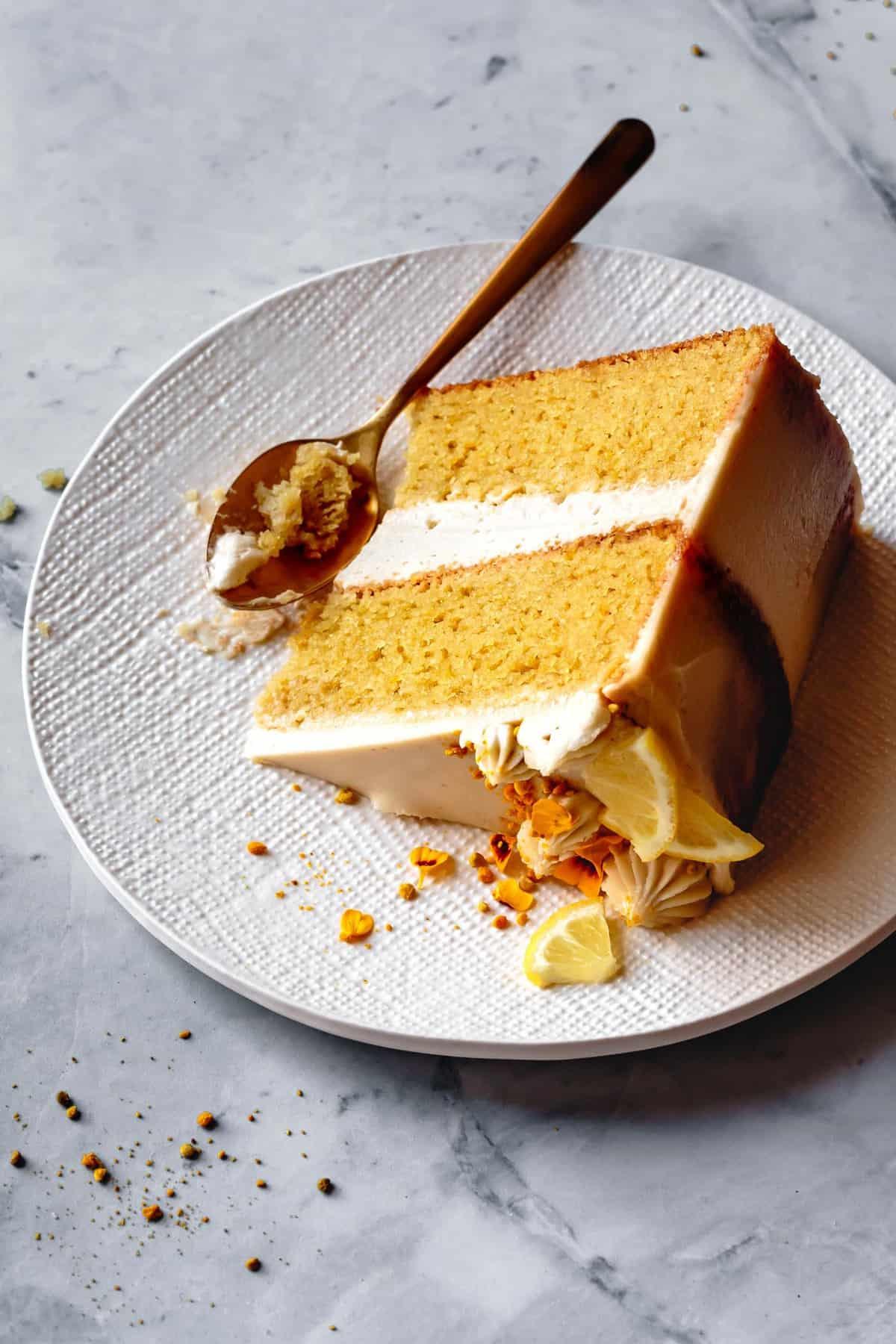 paleo lemon cake slice on a textured white plate on marble