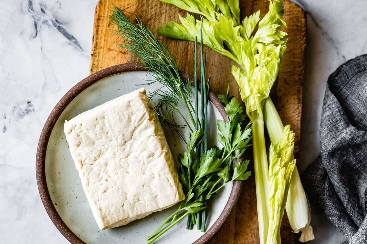 tofu on a plate with whole herbs and celery on a board