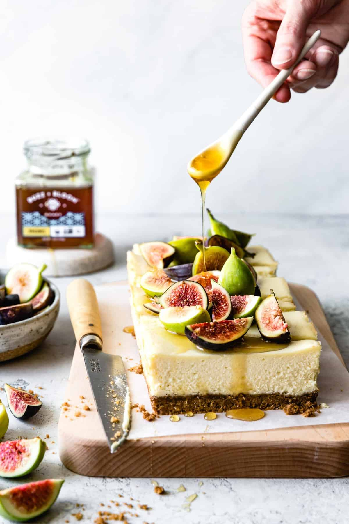 drizzling honey over fresh figs on GF cheesecake