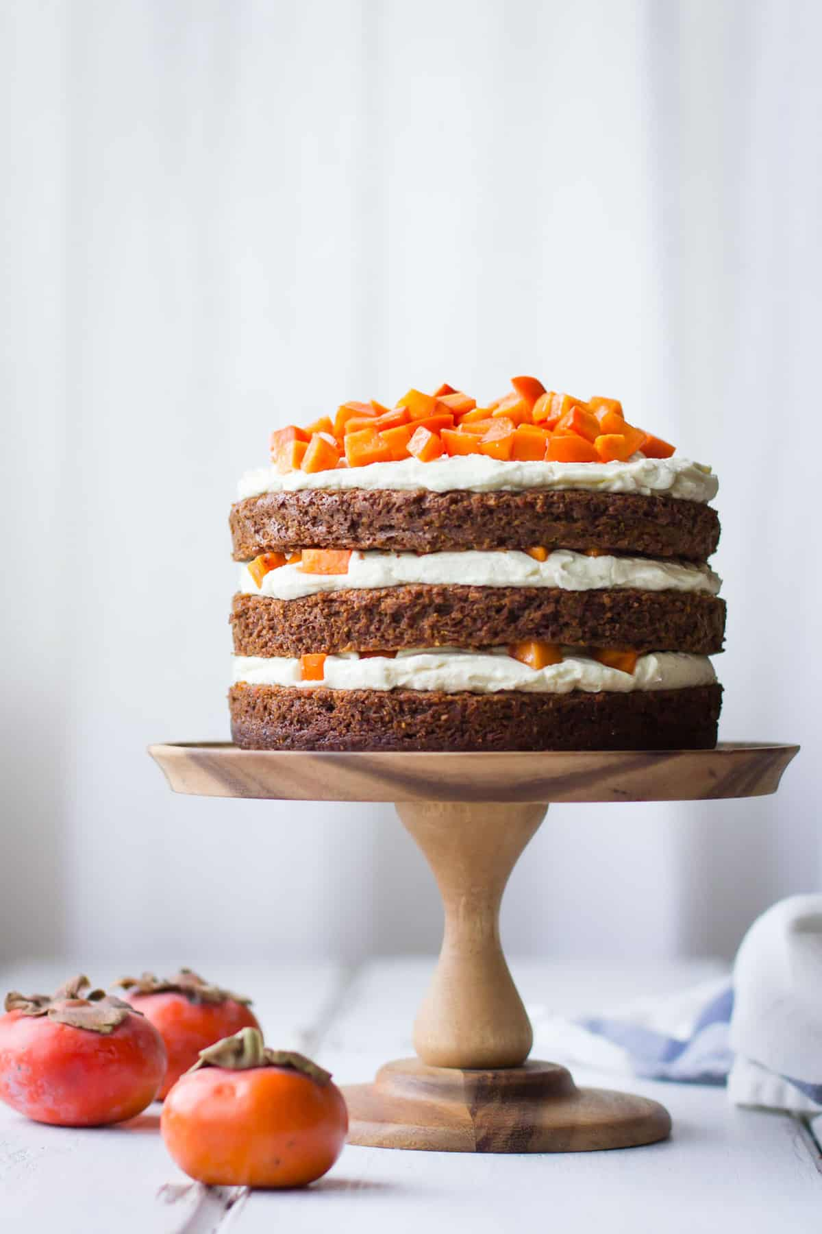 small persimmon layer cake on a wooden cake stand