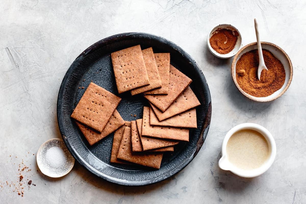ingredients for gf graham crust: graham crackers in a blue graniteware tin, salt, melted butter, coconut sugar, cinnamon