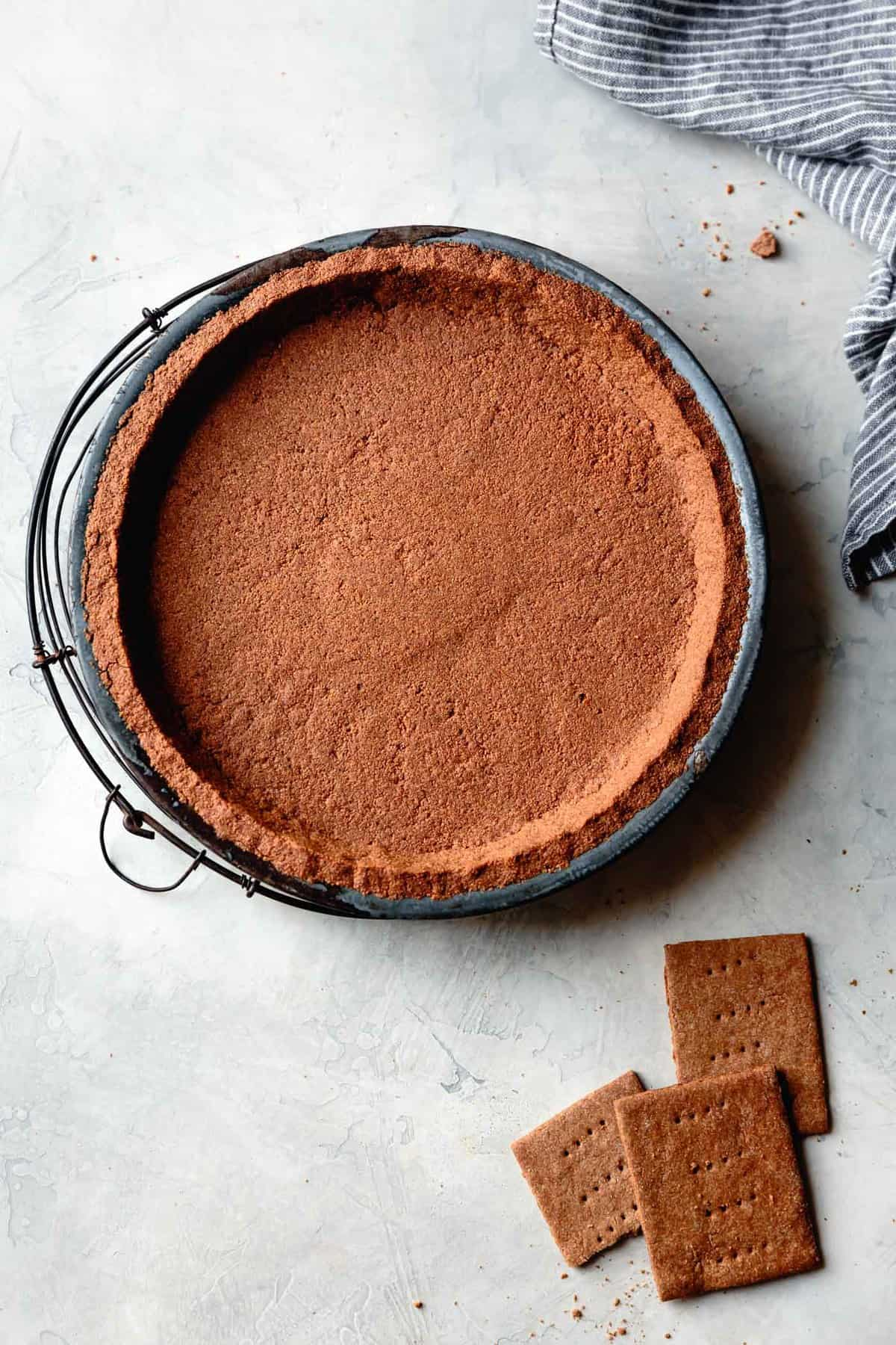 gluten-free graham cracker crust, baked and cooling on a plaster surface